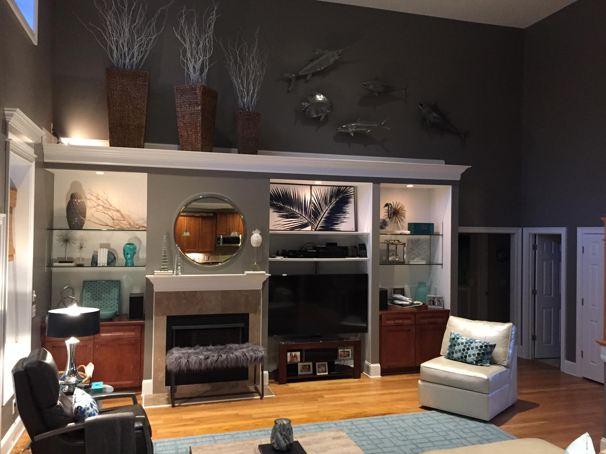 Book cases with tropical themed accessories and metal fish art hanging high on wall
