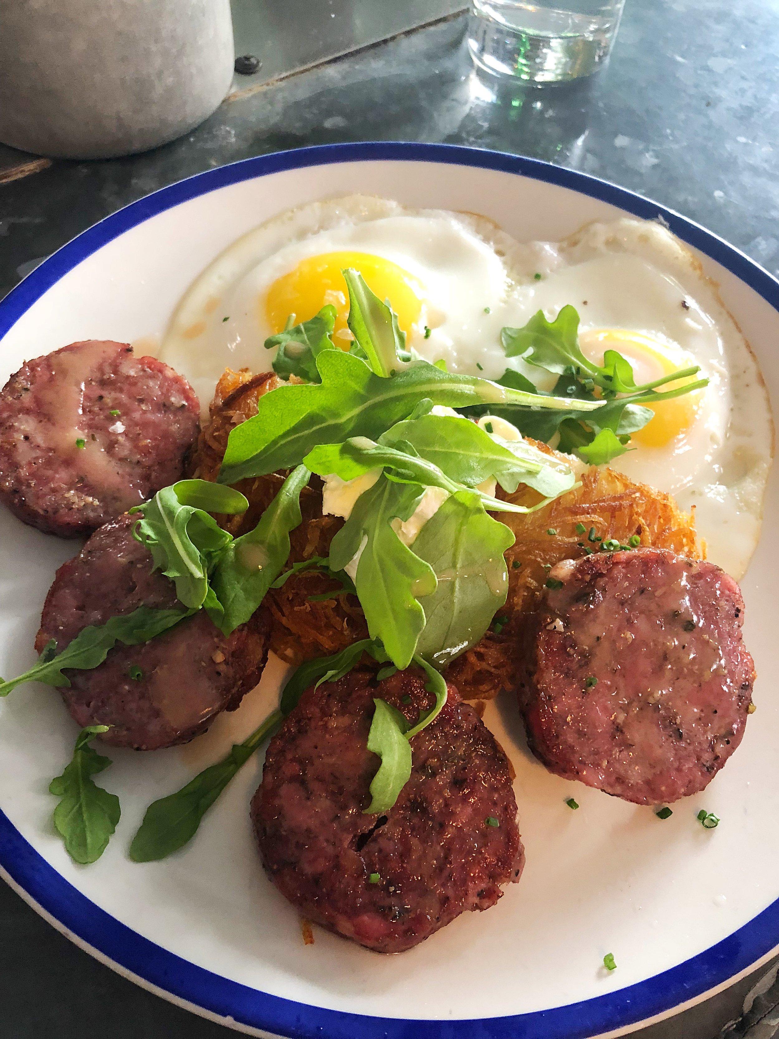 Saucisson a l'Ail: pork and garlic sausage, fried eggs, hashbrown, crème fraîche, arugula
