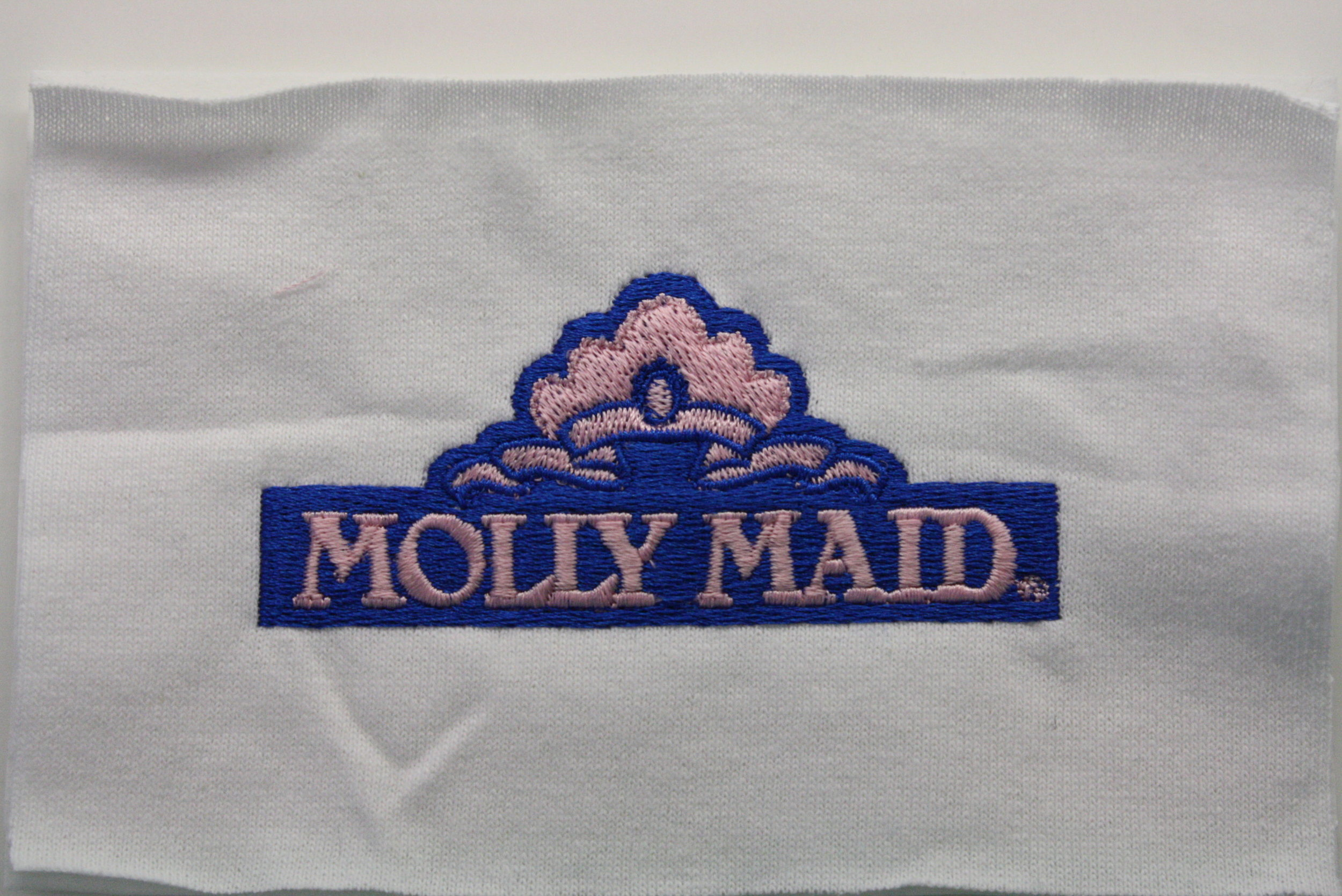 A previous logo for Molly Maid, sewn out on cutaway backing.