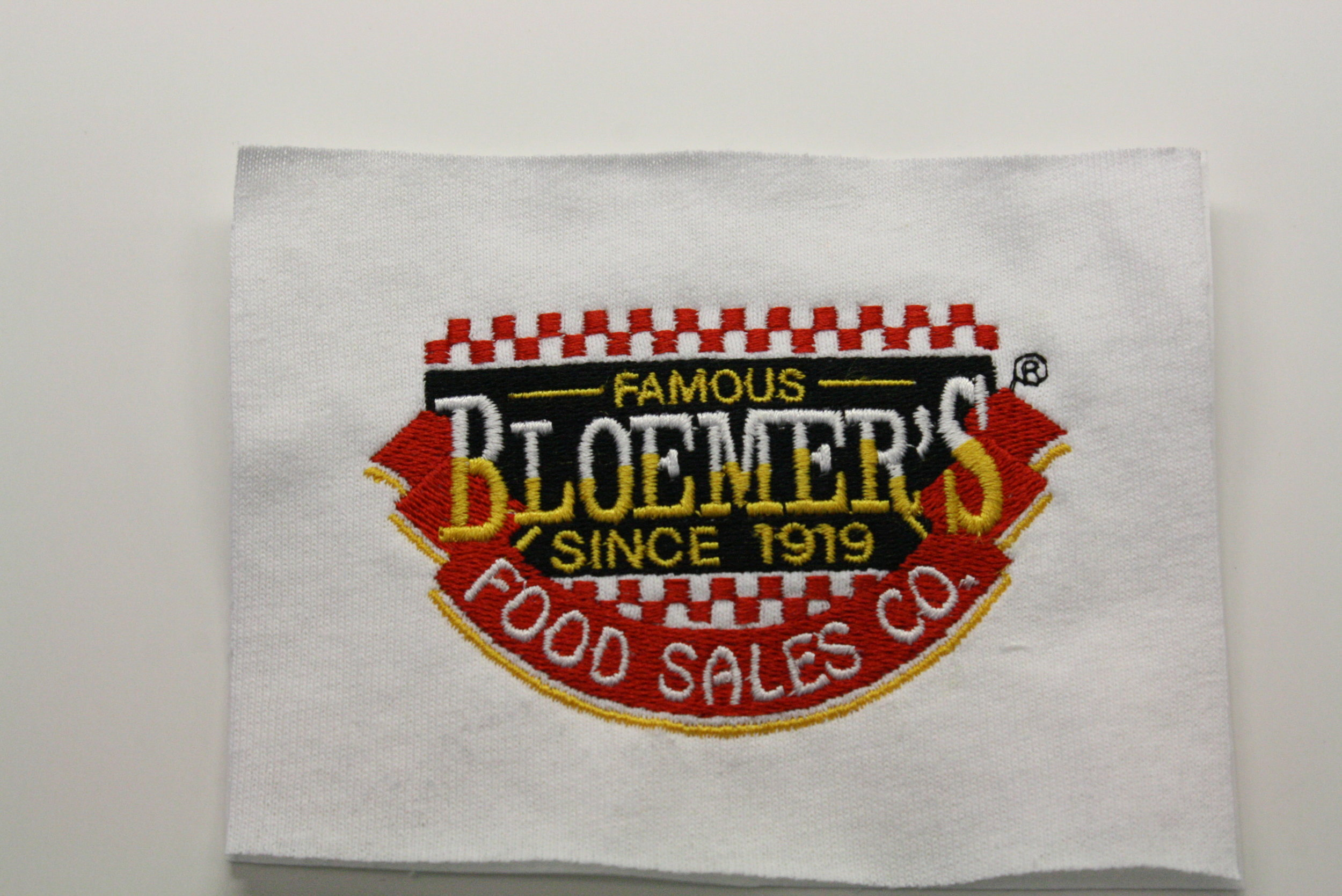 A sew out sample of Louisville's Bloemer's Food Sales logo.