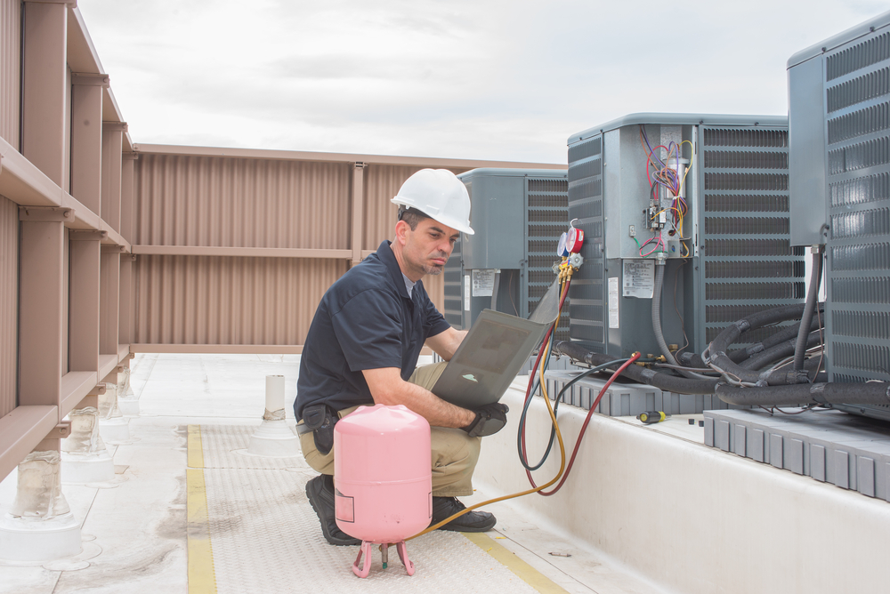 Technician looking at a panel off a condensing unit