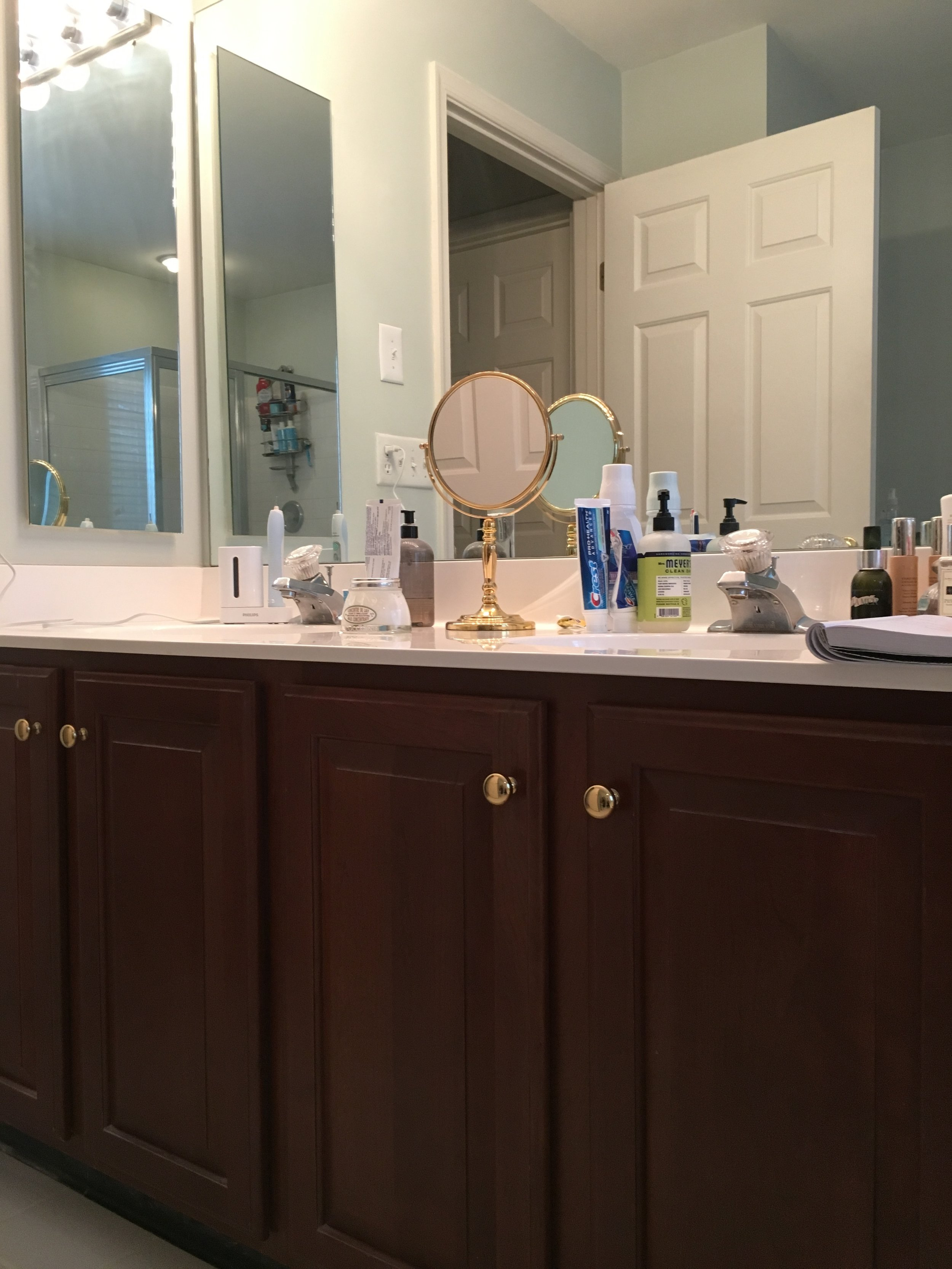 BEFORE: Too low cherry cabinet vanity with shiny brass pulls.