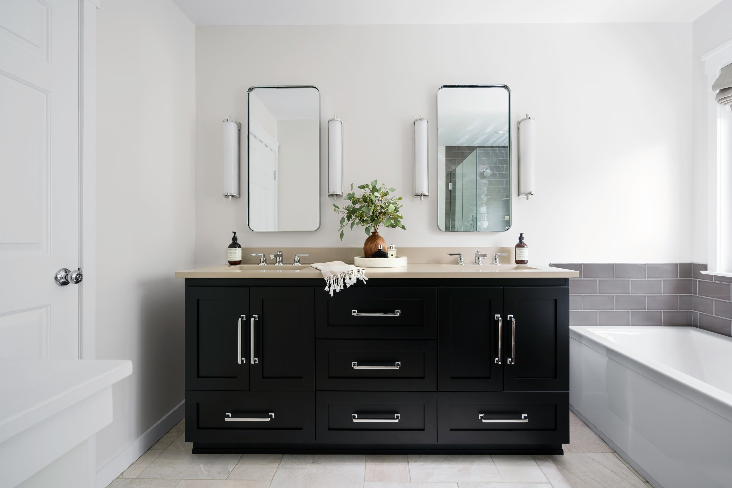 AFTER: Updated freestanding vanity with chrome finishes and sconce lighting.