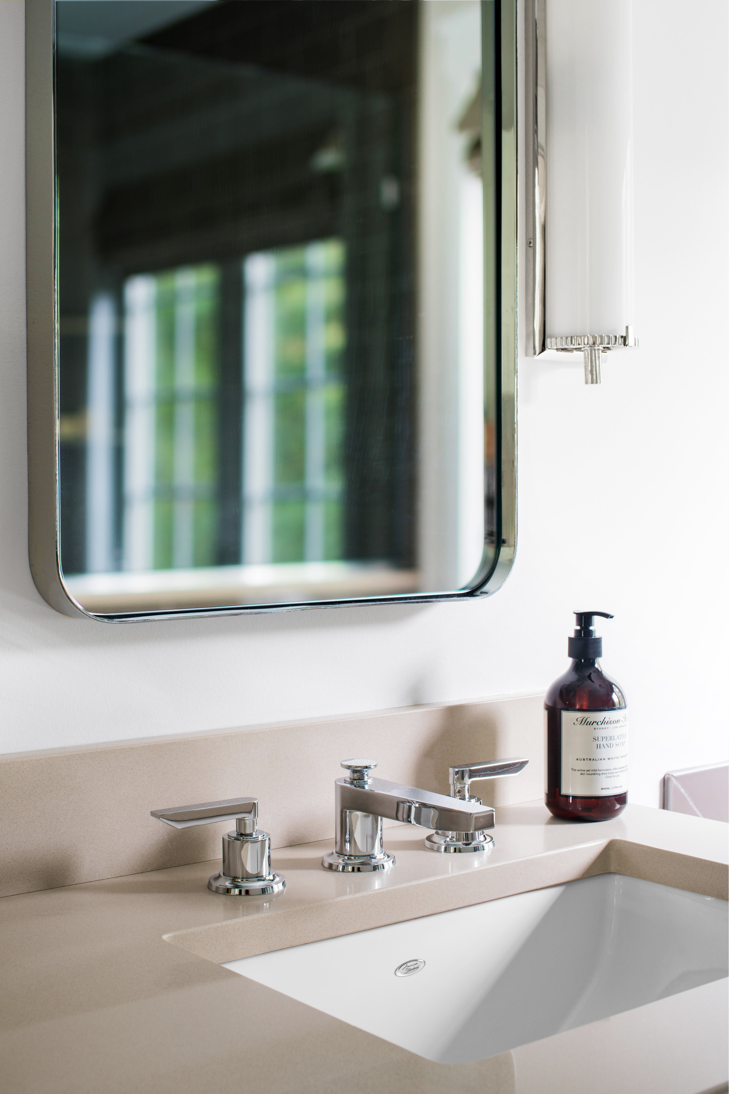 AFTER: Curved edge chrome mirrors with transitional California Faucets are a perfect balance.