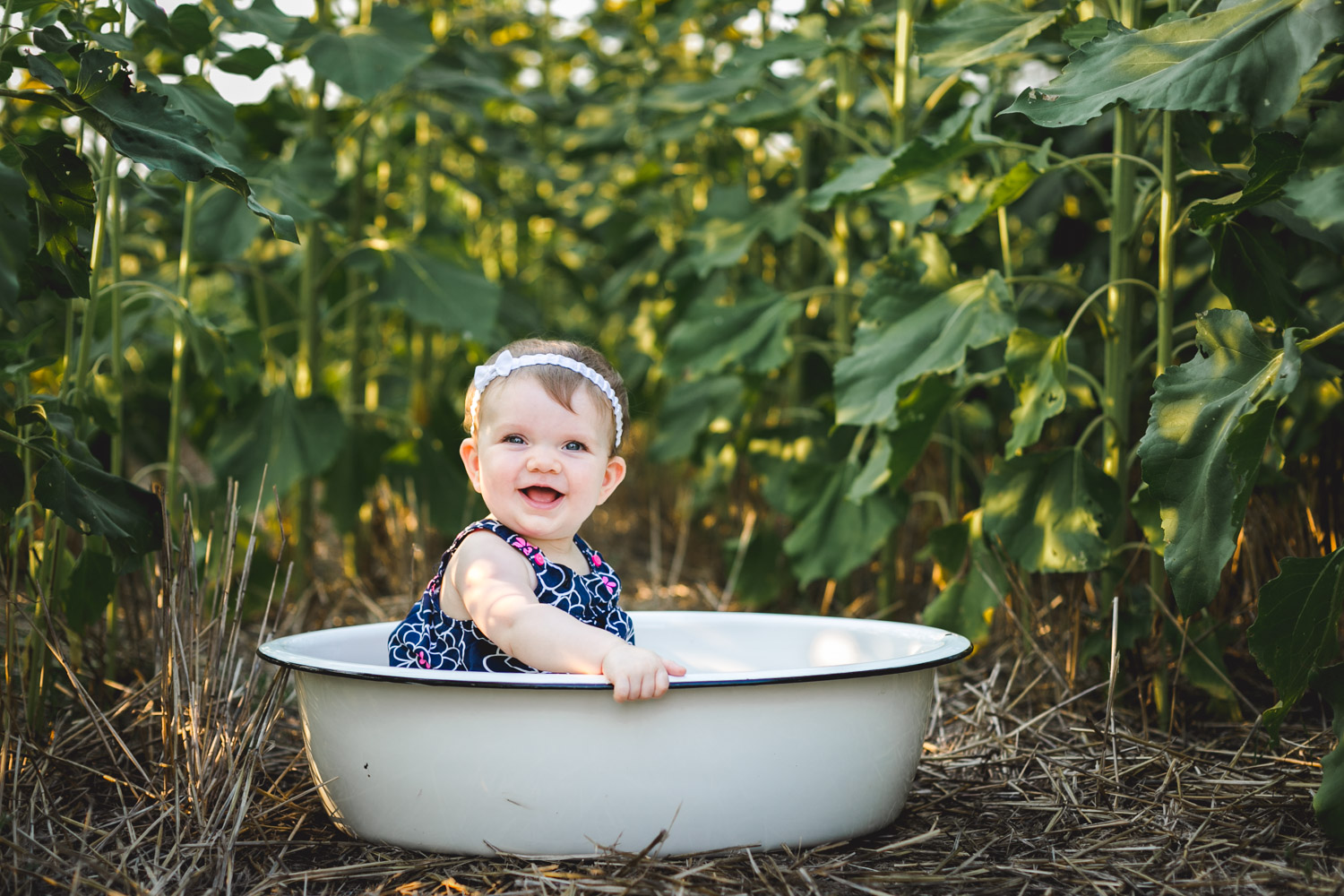 Baby sitting in the sunflower field during the fall at Britt's Garden Acres at a Family Photo Mini Session in Manhattan, Kansas.