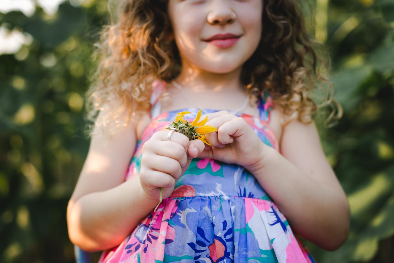 Girl holding a sunflower in the field at Britt's Farm and Garden Acres in Manhattan, Kansas.