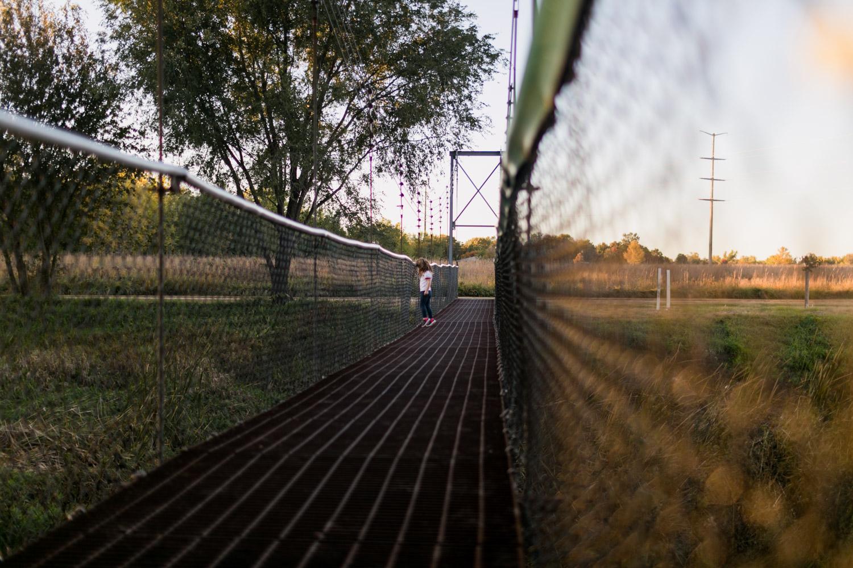 Documentary Lifestyle image of toddler on bridge. Captured by Manhattan Kansas Photographer, Renee McDaniel