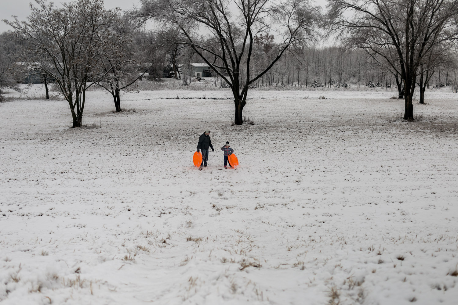Coming back up the hill after sledding down. Captured by best Lifestyle Family Photographer, Renee McDaniel in Manhattan, Kansas.