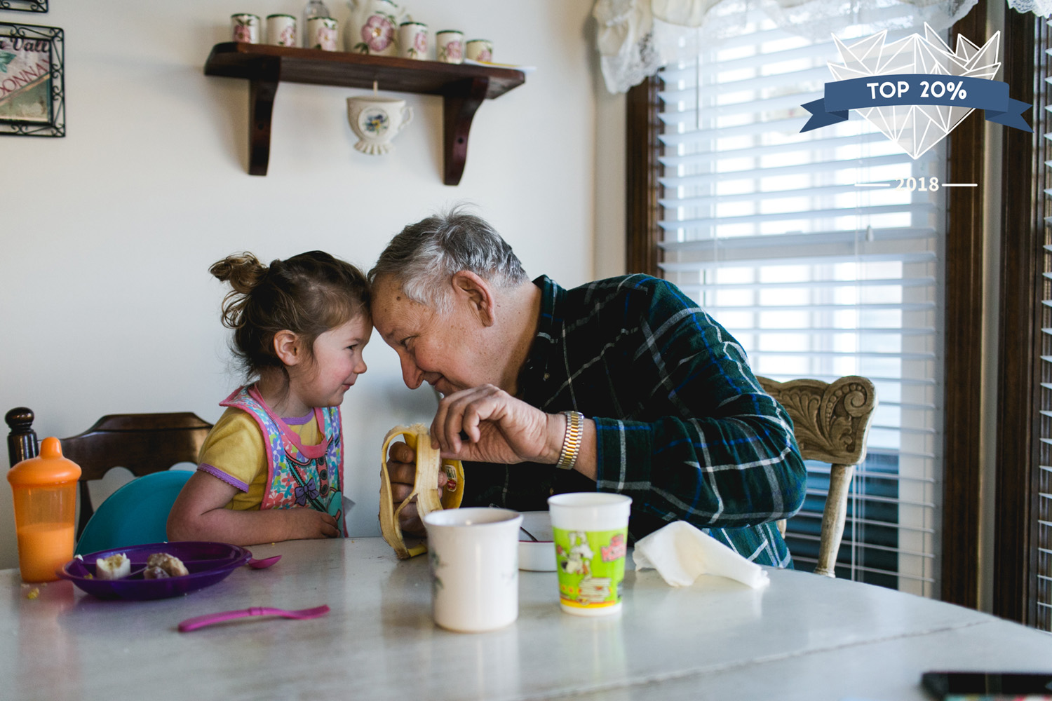 Little girl and her grandpa sitting head-to-head, touching foreheads, while eating breakfast in Olathe, Kansas.