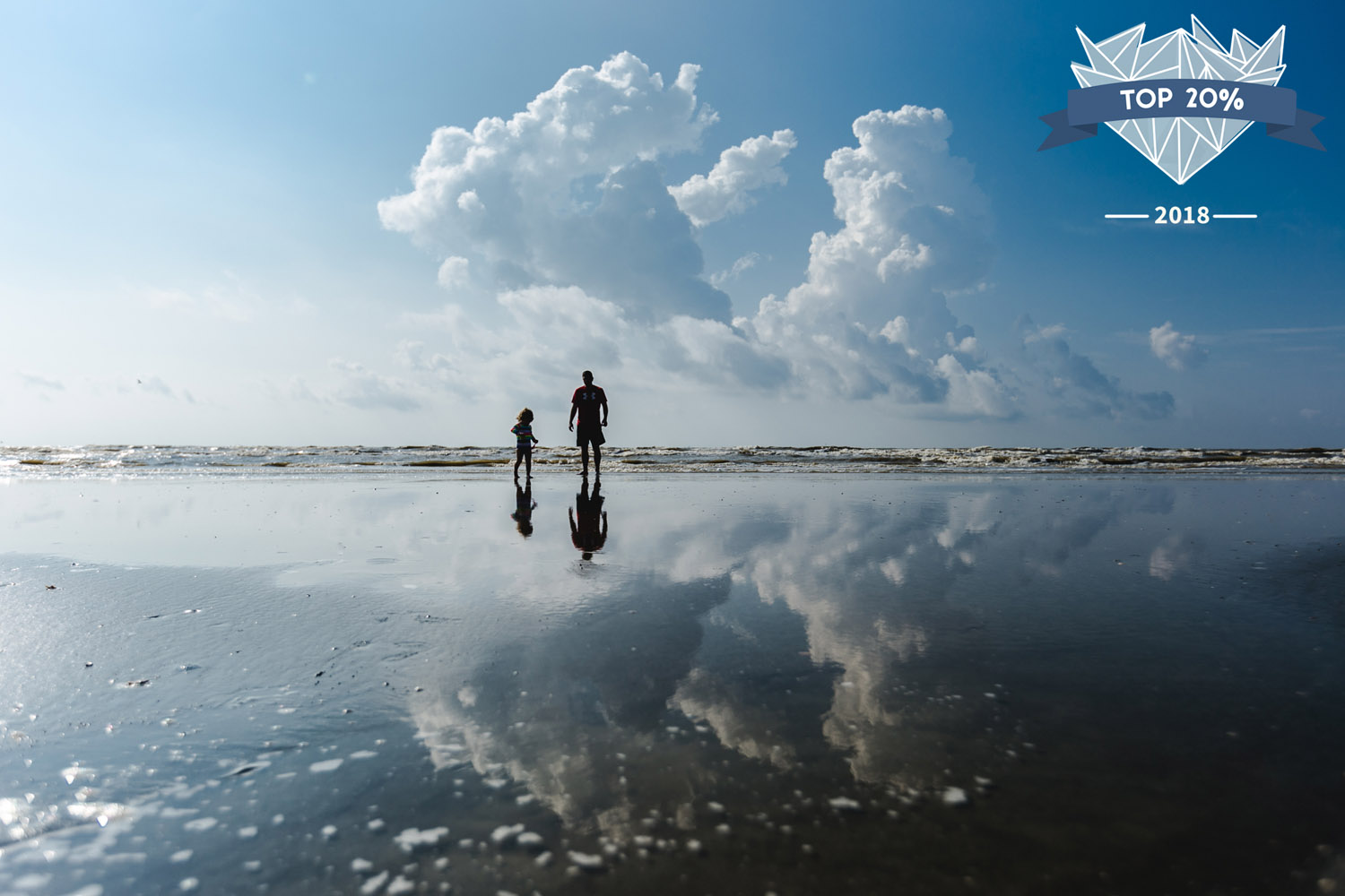 Girl and Father out playing along the shore in Galveston, Texas, their silhouettes reflected in the water on the sand. Photographed by best family and child documentary photographer, Renee McDaniel Photography based in Manhattan, Kansas