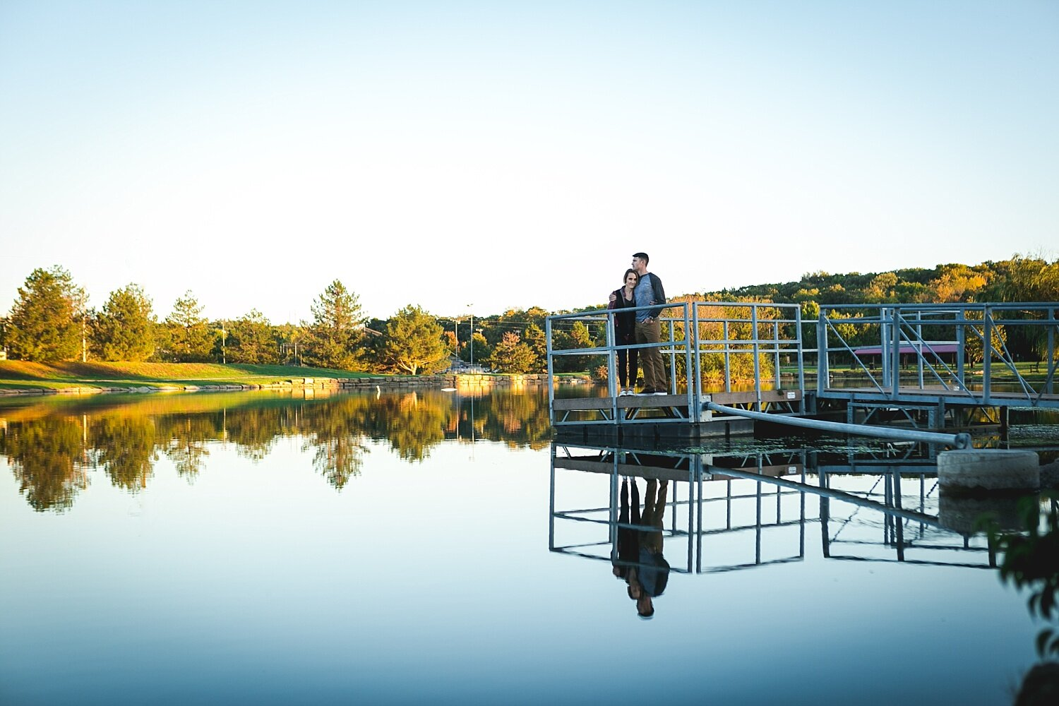 Couple poses on a dock at the fishing pond at Anneberg Park in Manhattan, KS