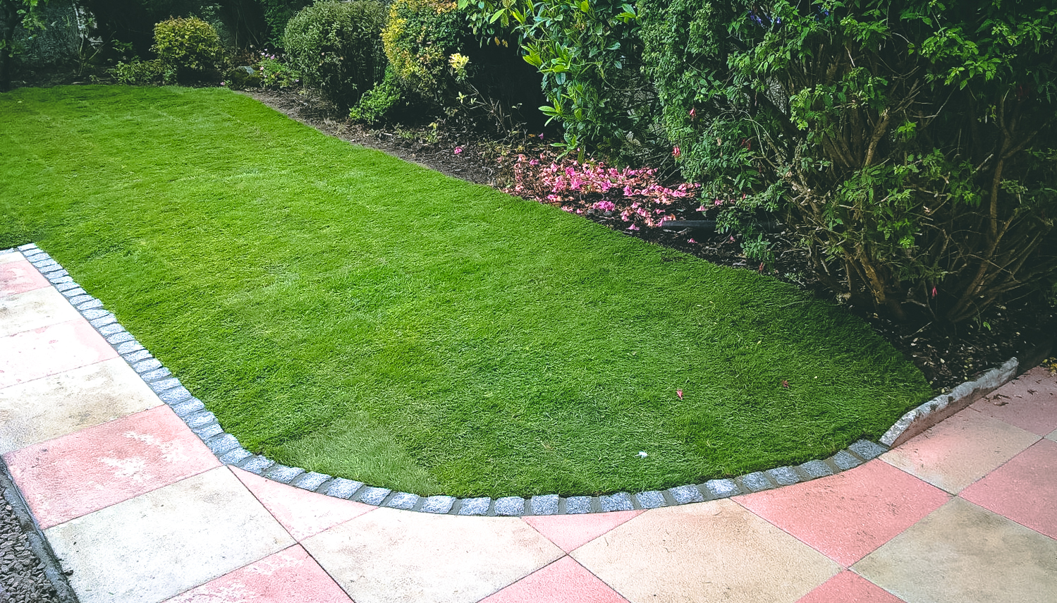 New slabbed area with granite edging and lawn