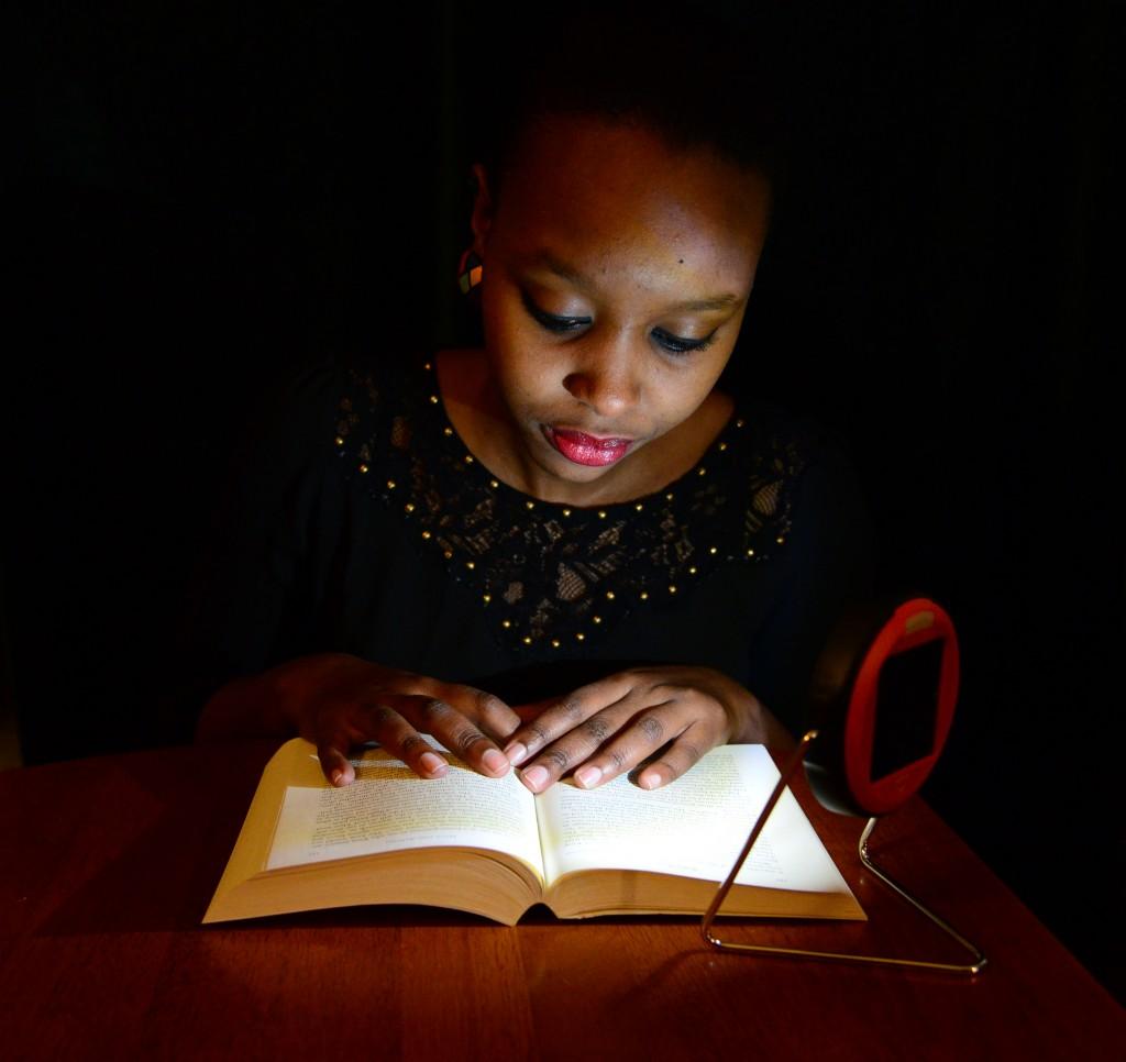 Westminster College student Sandra Nivyabandi, who is from Burundi and Rwanda,demonstrates using one of the solar lamps to be sent to primary students in Rwanda.