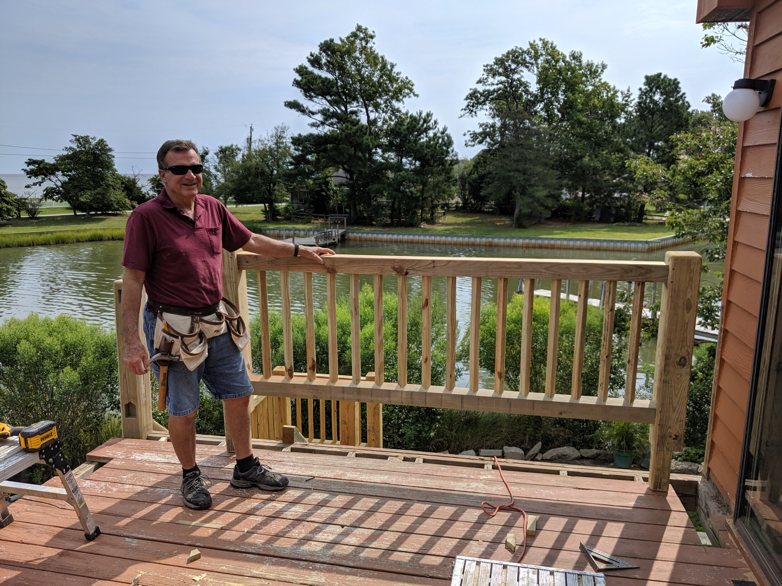 """rick holding an """"upgraded"""" version of our railing system featuring rotated pickets mortising into the top and bottom rails. The entire railing section interlocks into corresponding sockets, called mortises. (see post on left side of image) the entire assembly is then installed into place."""