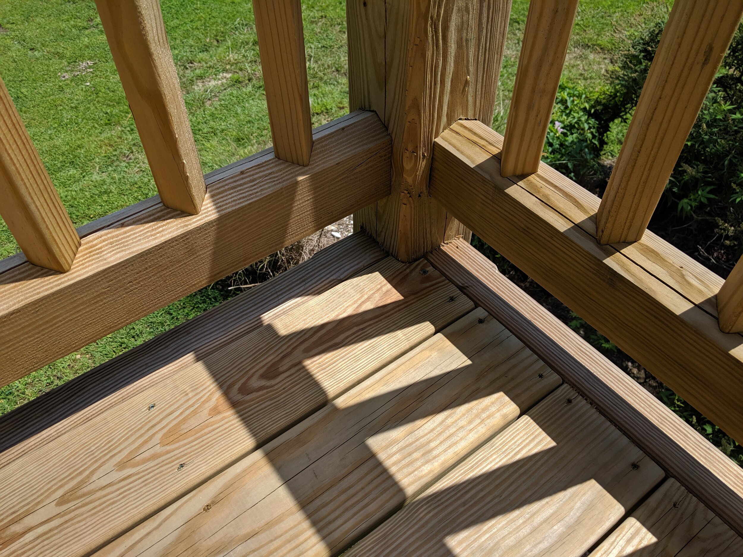 a close up of a typical railing-to-post connection featuring rotated pickets. note the slight angle at the top of the bottom rail, which helps shed water off of the railing