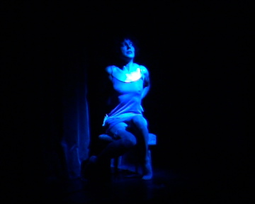 Baggage - Live performance with sound.Absolute darkness. Centre stage a blue light (from overhead) fades up making a pool of light. A girl sits, poised, composed, still. She is on small white stool and wears a thin dress, high heels and stockings. Her hair is black, cut in a short bob. Facing stage left. Soundtrack begins – a staggered monolgue against a repeating tone. The voice is female, deprecating & mean.The subject matter of the monologue is dark – the voice talks of death, of loss and breakdown. It proposes that the audience see her as being trapped in a kind of limbo, perhaps in the moments between the end of her life and death itself – not so much 'going into the light' but rather suspended within the full glare of it.Duration 7.5 minutes
