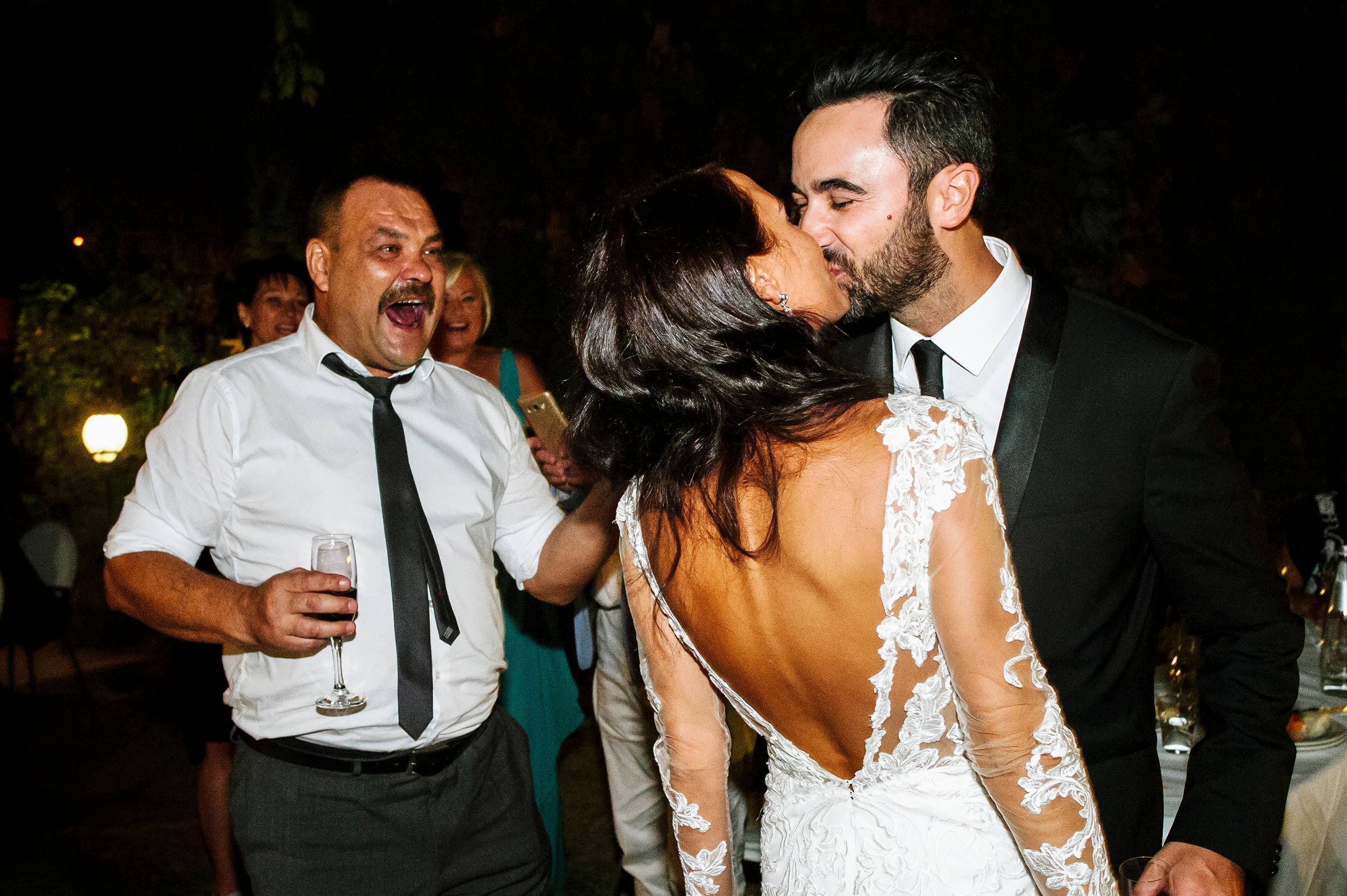 bride-and-groom-kissing-in-front-of-brides-father.jpg