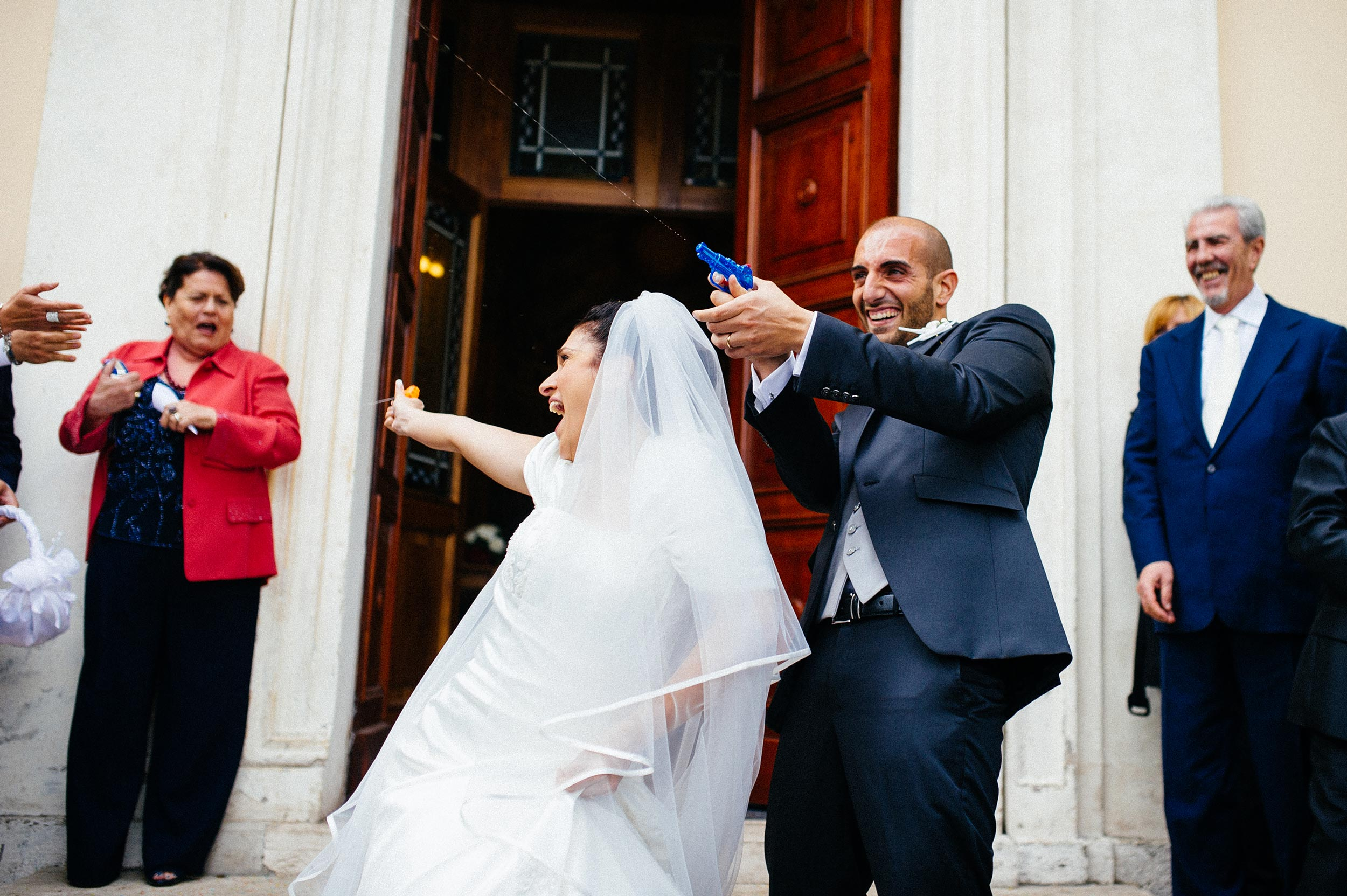 bride-and-groom-outside-the-church-shoot-guests-with-water-guns.jpg