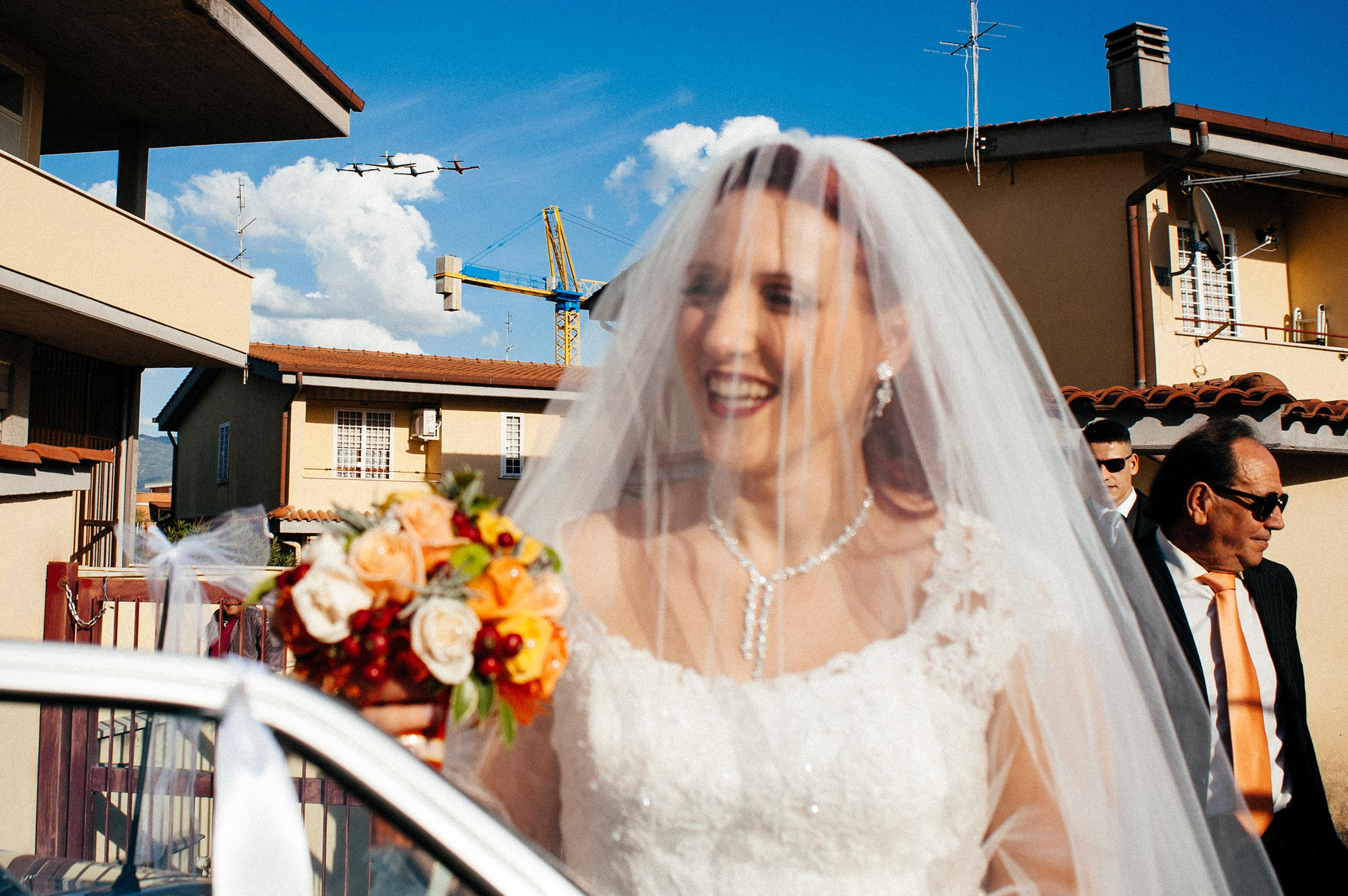 bride-going-to-ceremony-while-aircrafts-pass-over-her-head.jpg