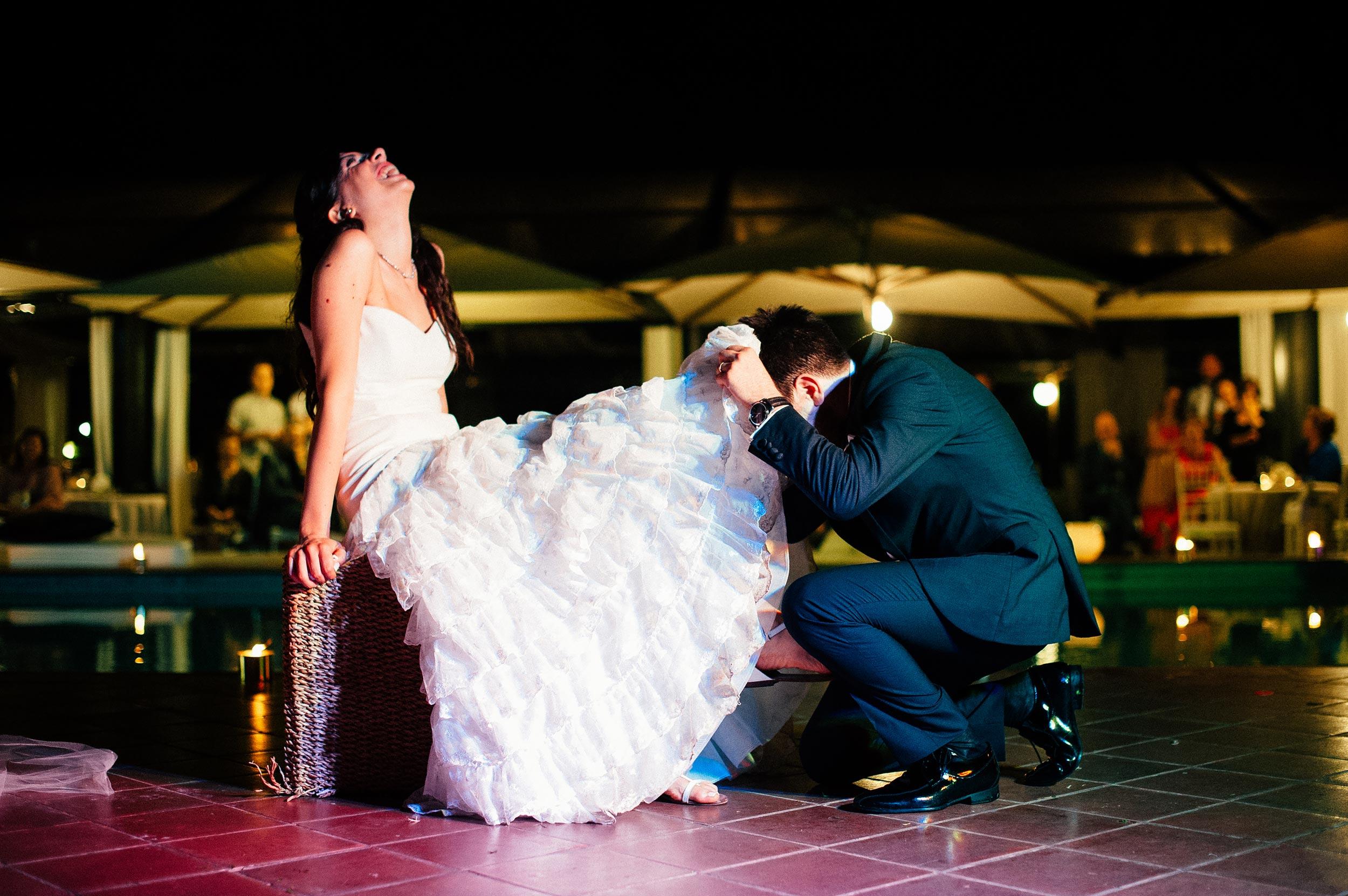 groom-looking-under-brides-wedding-dress-aiming-for-the-garter.jpg