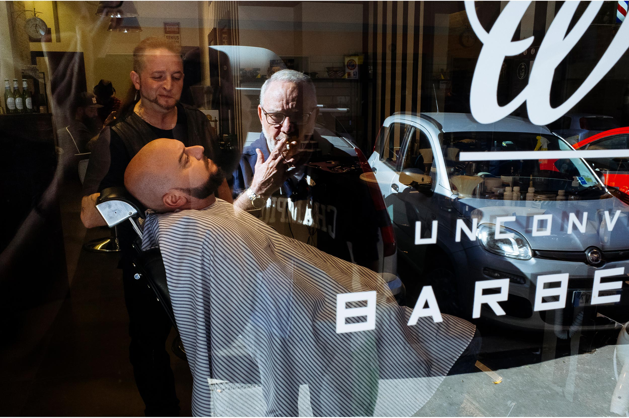 groom-getting-ready-in-the-barbershop-while-his-dad-watches-outside.jpg