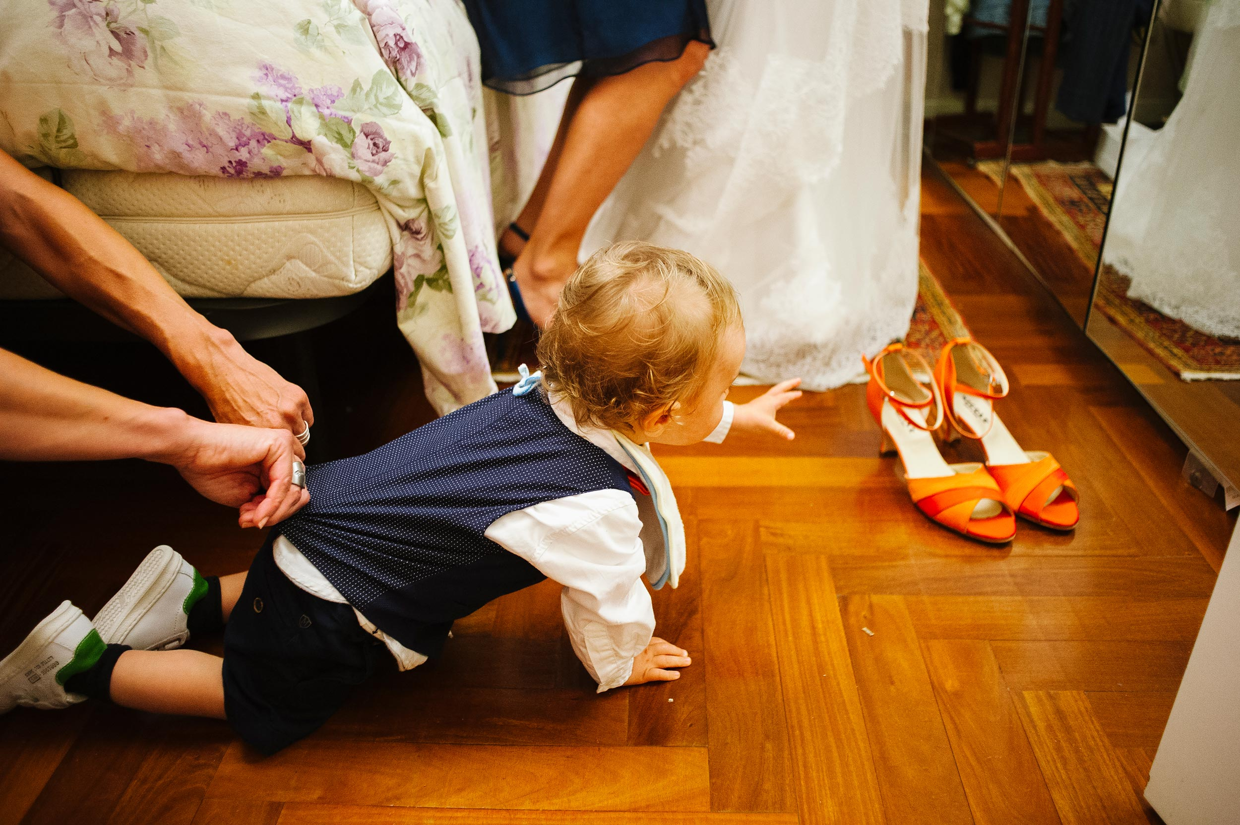 kid-aims-for-brides-shoes-while-his-mom-holds-him.jpg