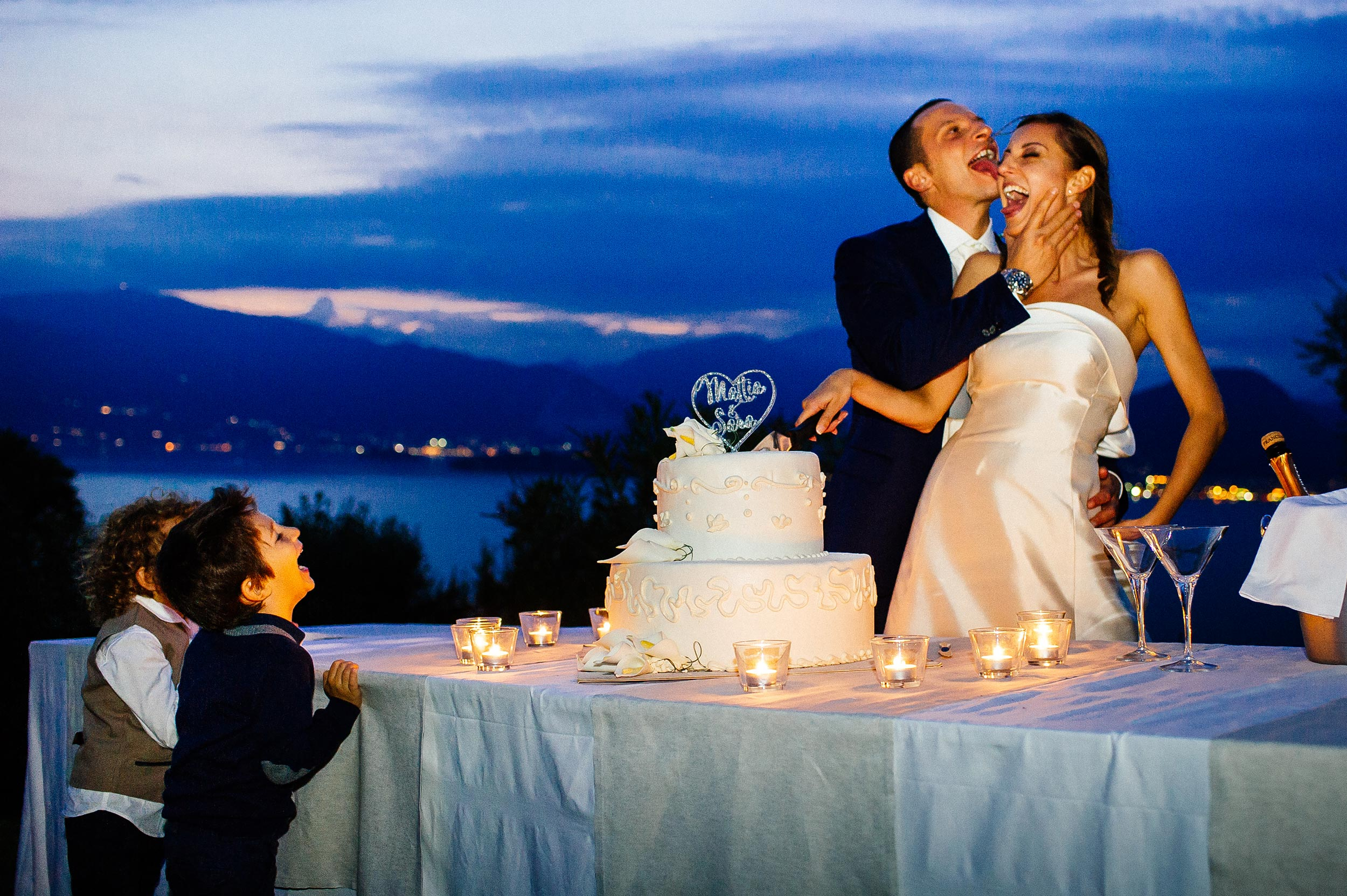 kids-laugh-at-groom-licking-brides-face-during-cake-cutting-colors.jpg
