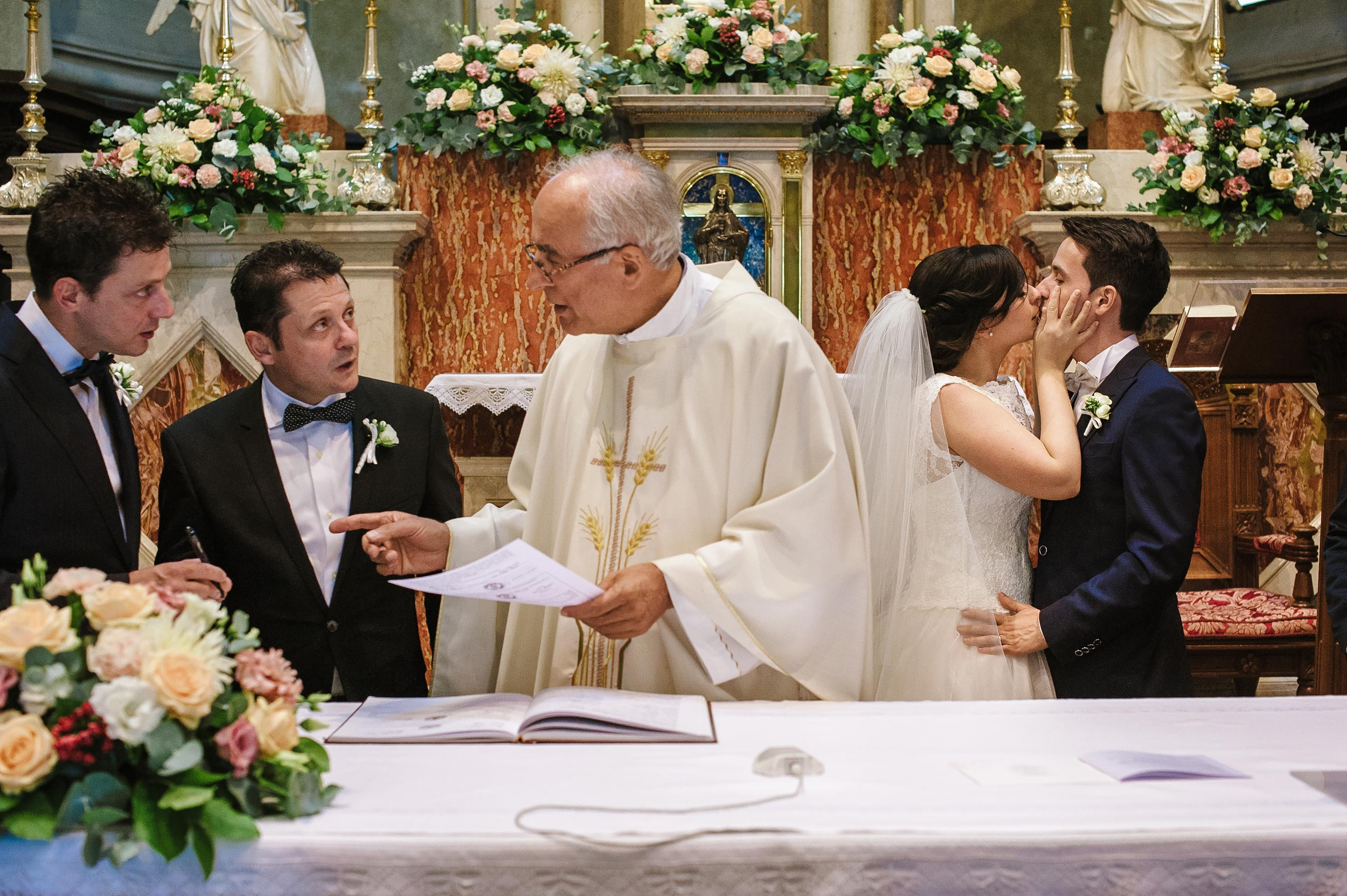 the-bride-kisses-the-groom-in-church-while-witnesses-wait-to-sign.jpg