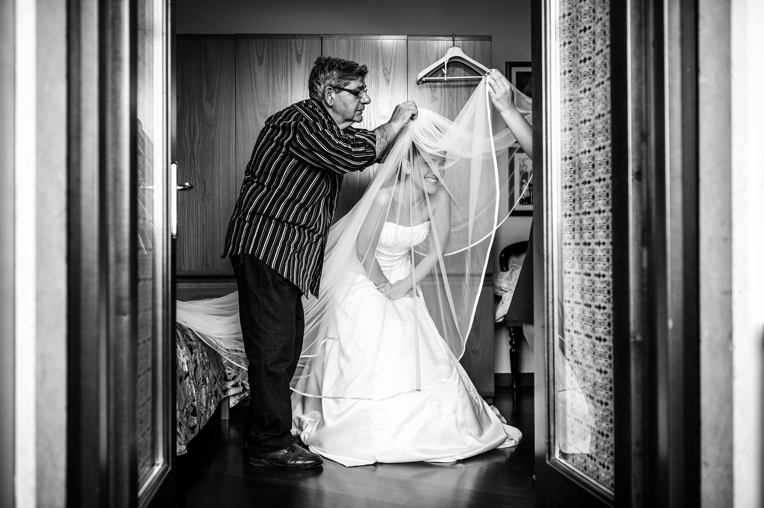 bride-getting-ready-helped-by-a-man-putting-the-veil-on-black-and-white-wedding-photography.jpg