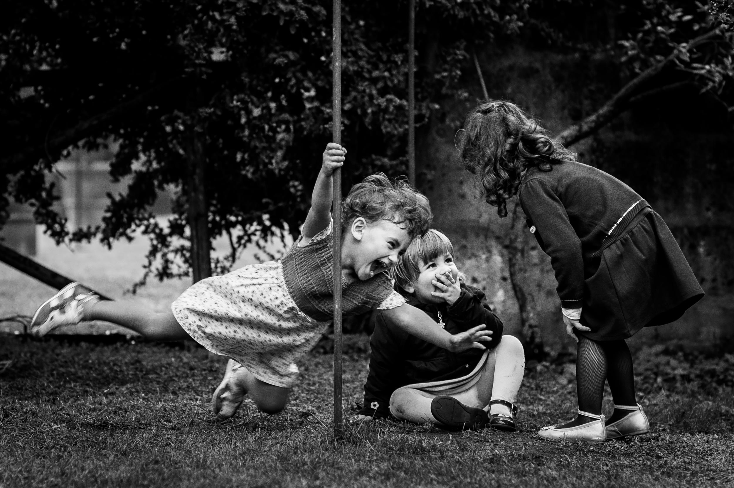girl-playing-with-a-pole-among-children-black-and-white-wedding-photography.jpg