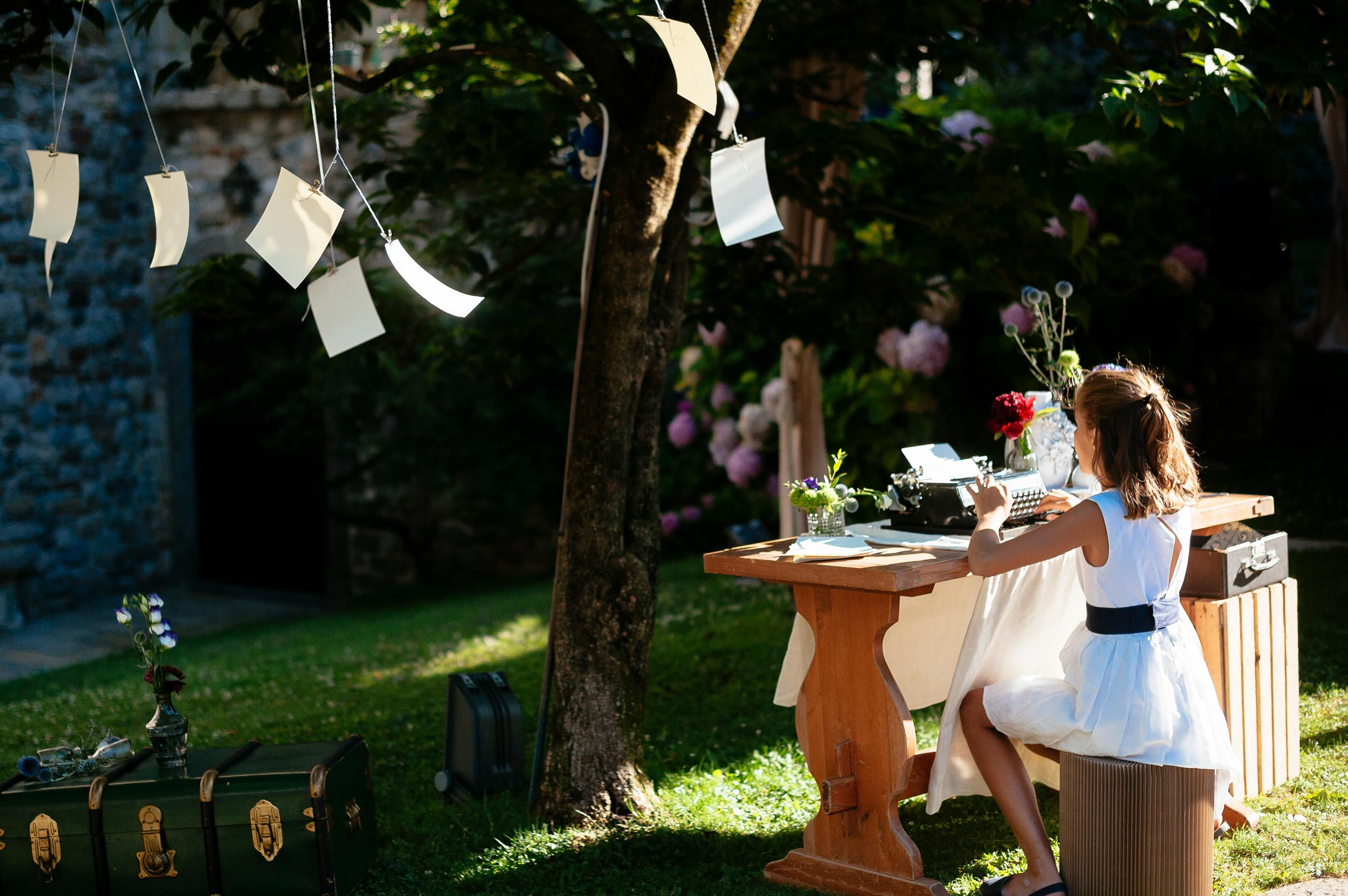 girl-using-typewriter-during-wedding-reception-in-italy-paper-sheets-flow-with-the-wind.jpg