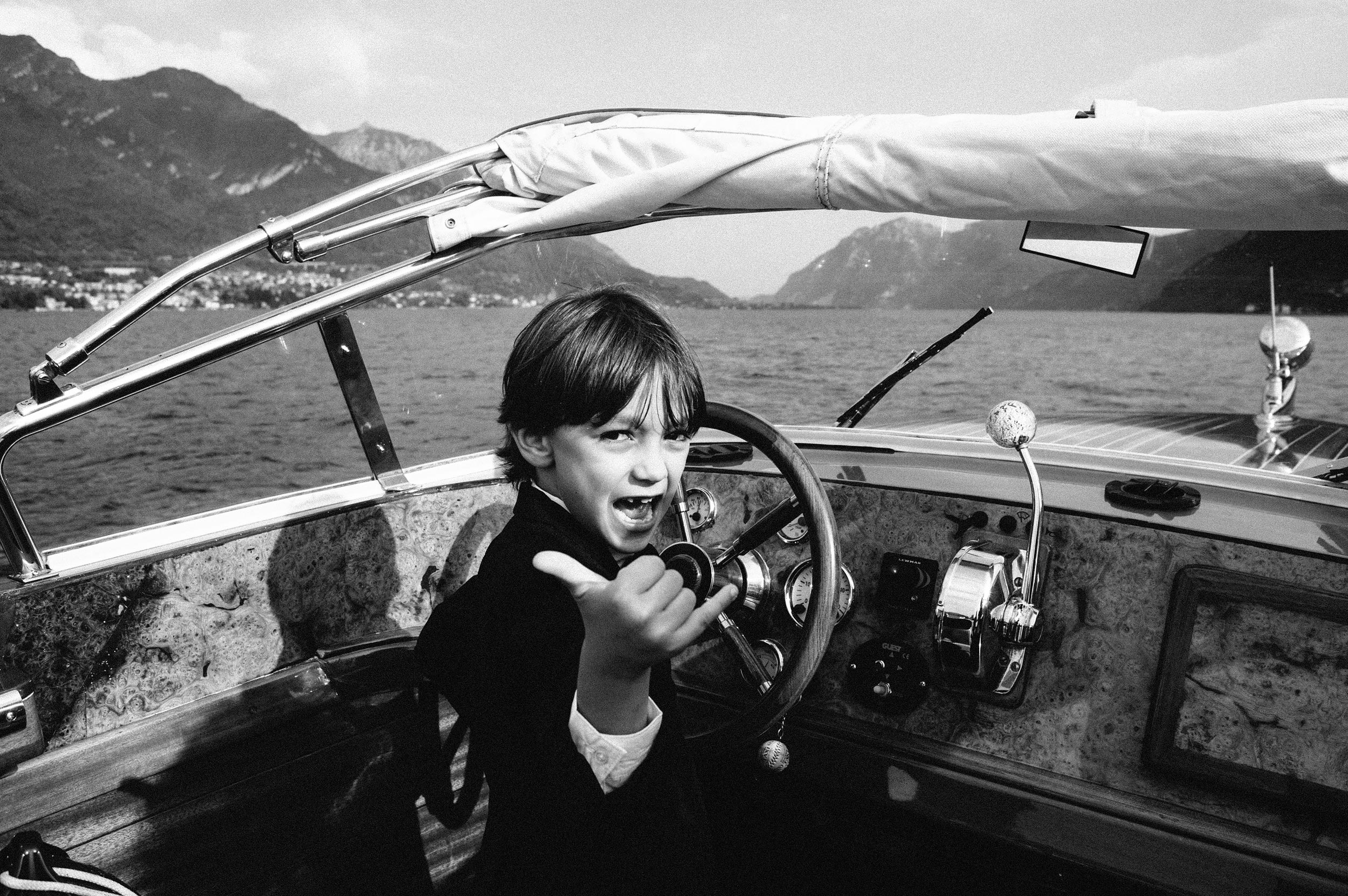 kid-driving-a-motorboat-on-lake-como-black-and-white-wedding-photography.jpg