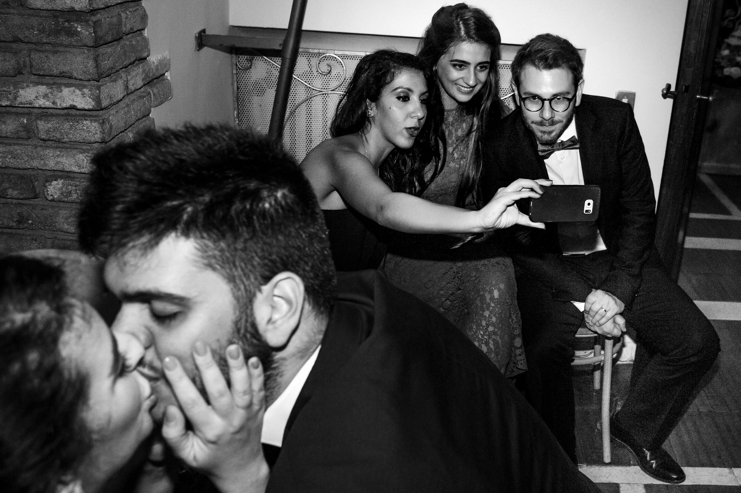 selfie-at-wedding-while-another-couple-kisses-multi-subject-street-photography-black-and-white-wedding-photography.jpg