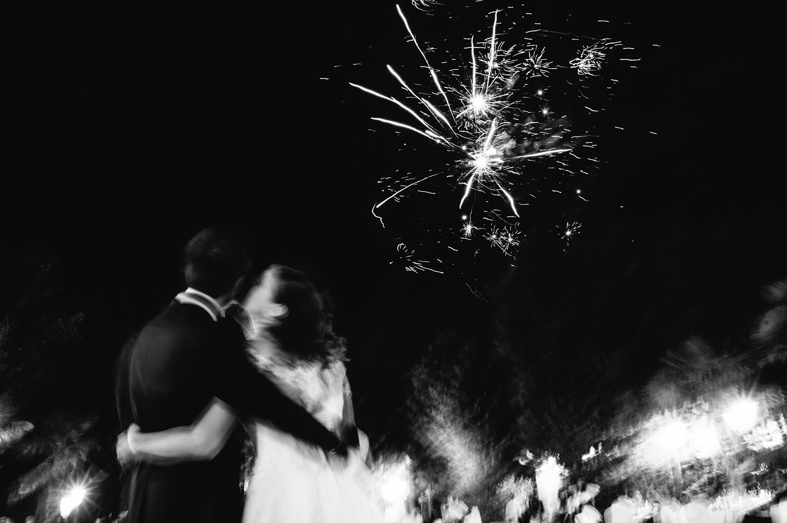 the-bride-kisses-the-groom-under-fireworks-black-and-white-wedding-photography.jpg