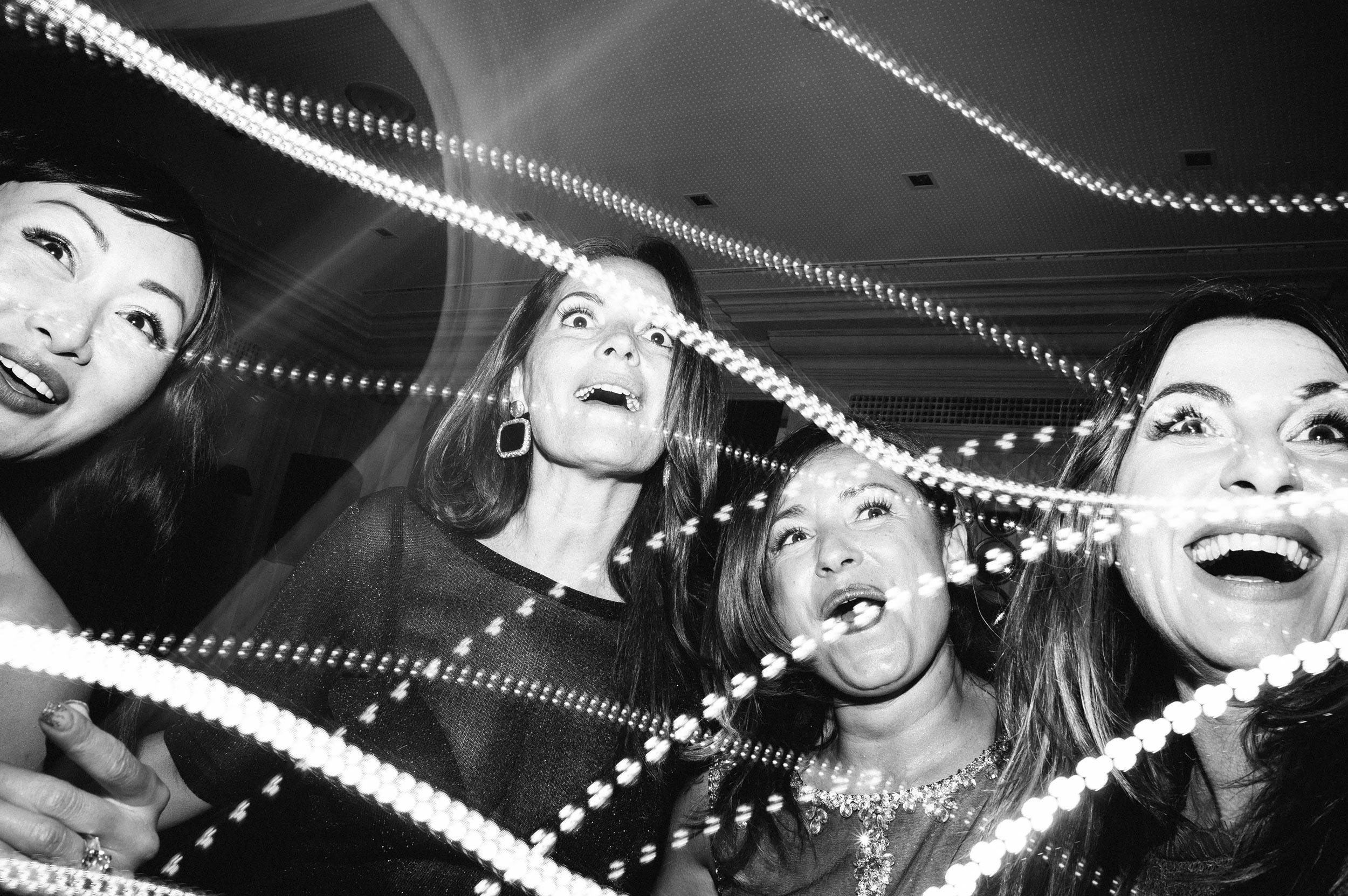astonished-women-among-lights-during-wedding-reception-black-and-white-wedding-photography.jpg
