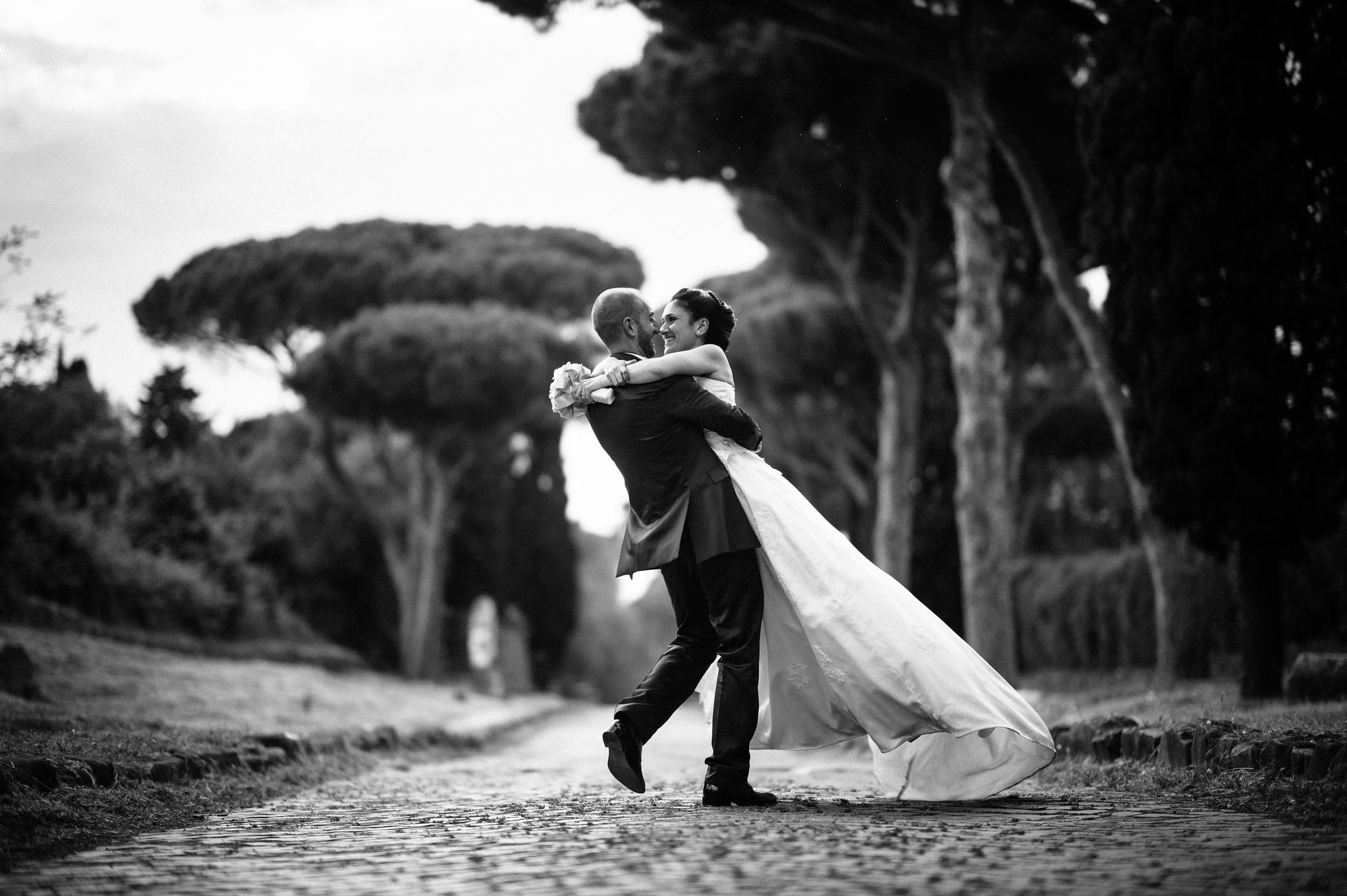 via-appia-antica-bride-and-groom-holding-and-dancing-black-and-white-wedding-photography.jpg