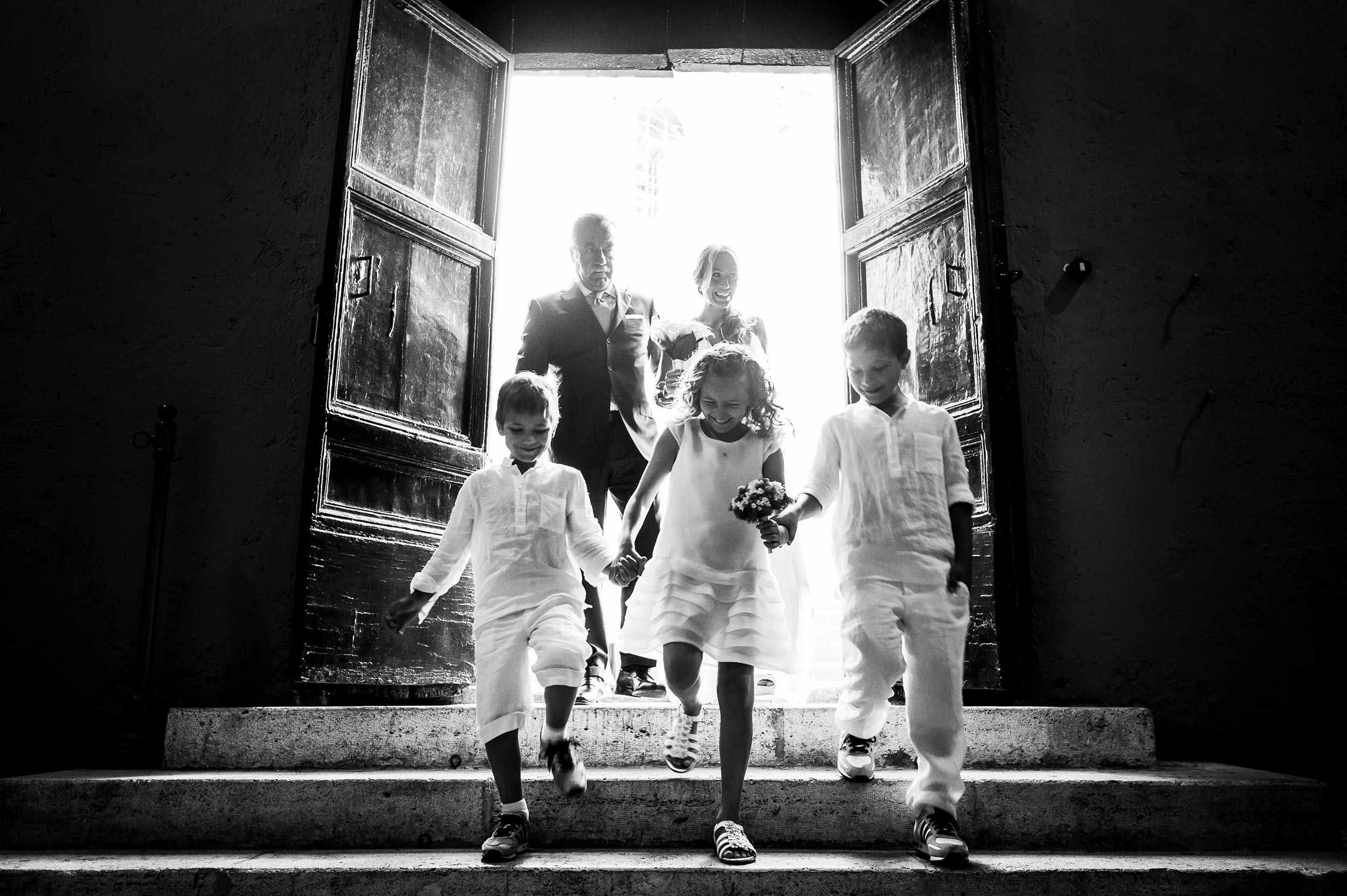 bride-and-dad-enter-church-with-three-kids-down-the-steps-vatica-city-rome-black-and-white-wedding-photography.jpg