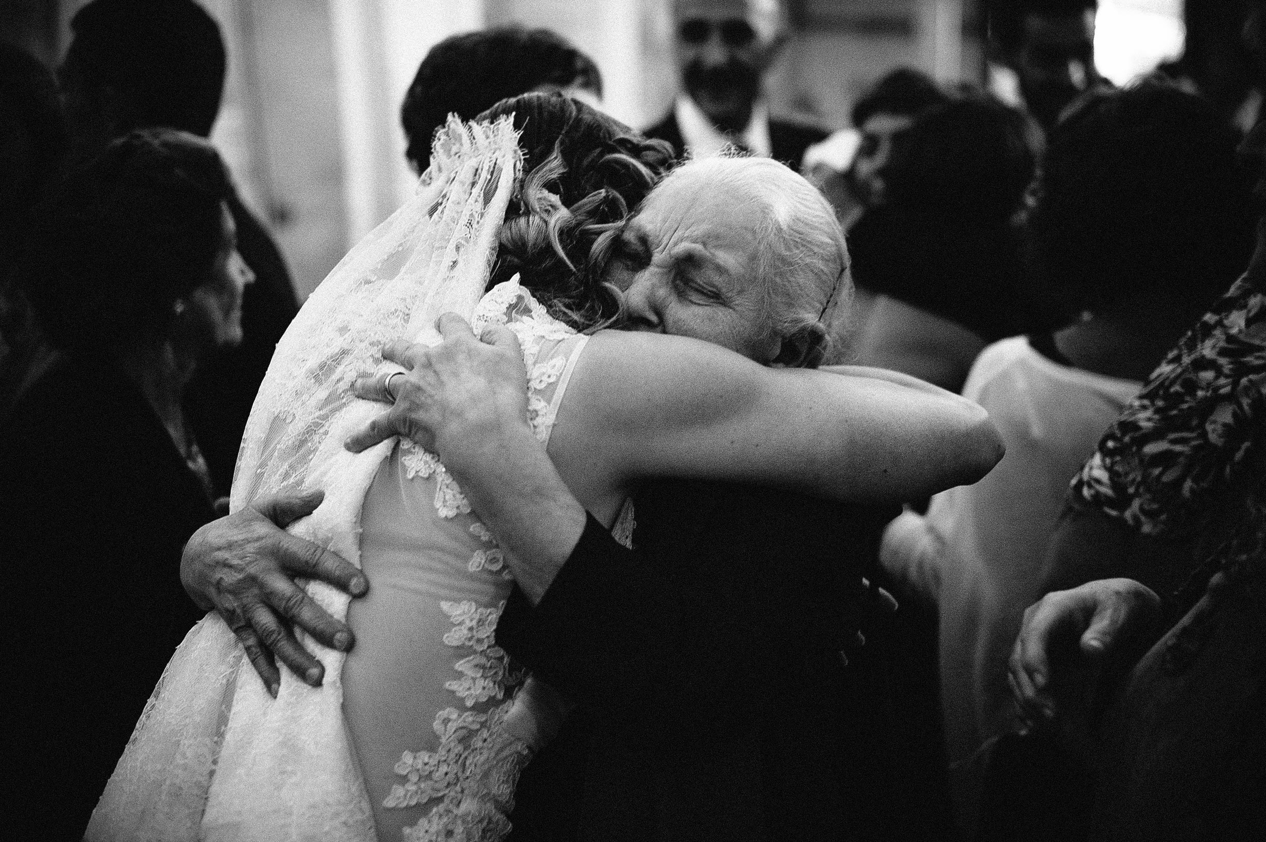 the-bride-hugs-her-grandmother-after-the-reception-italy-black-and-white-wedding-photography.jpg