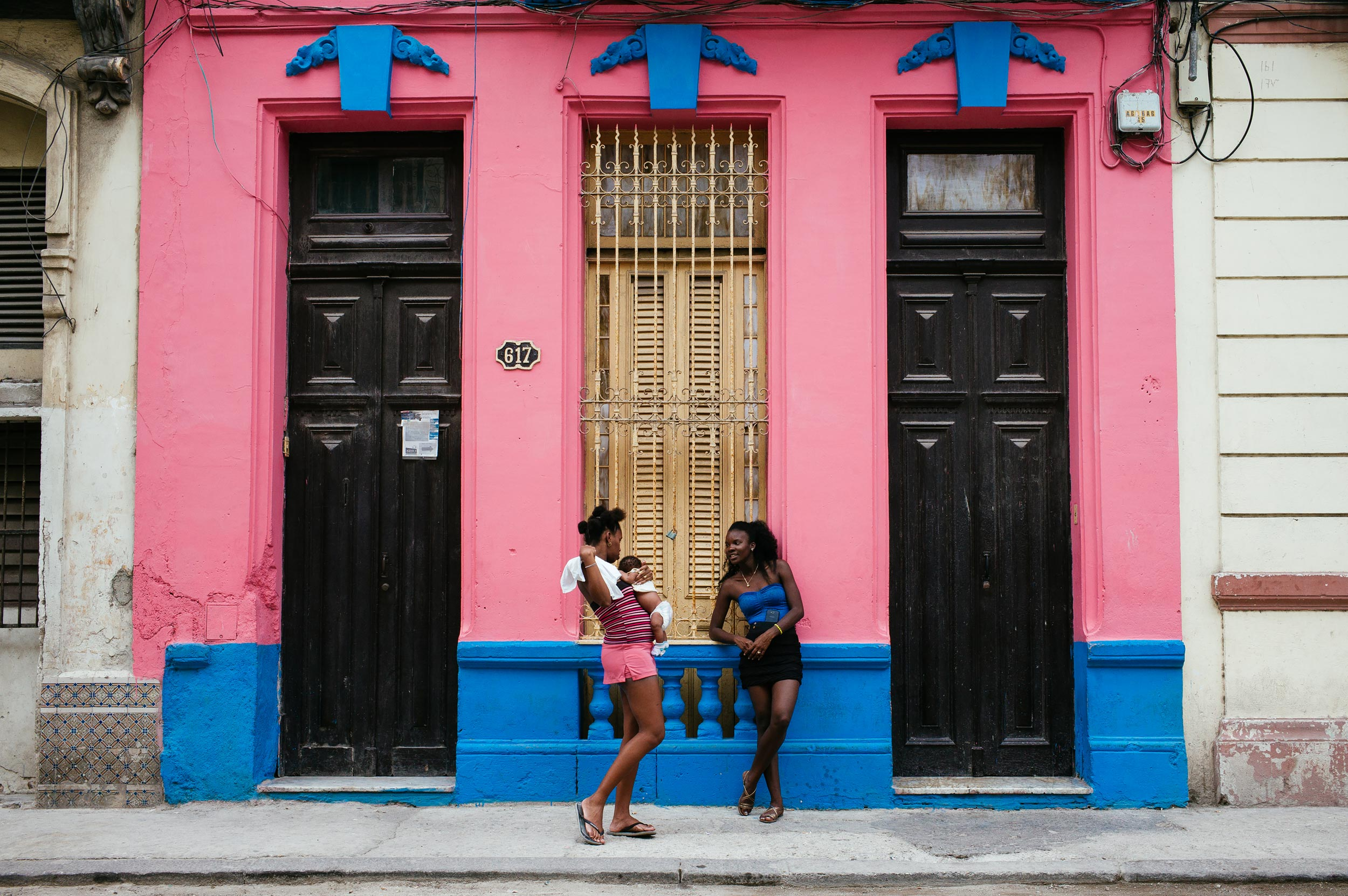 La-Habana-2016-two-ladies-standing-building-has-colors-of-their-clothes-street-photography-by-Alessandro-Avenali.jpg