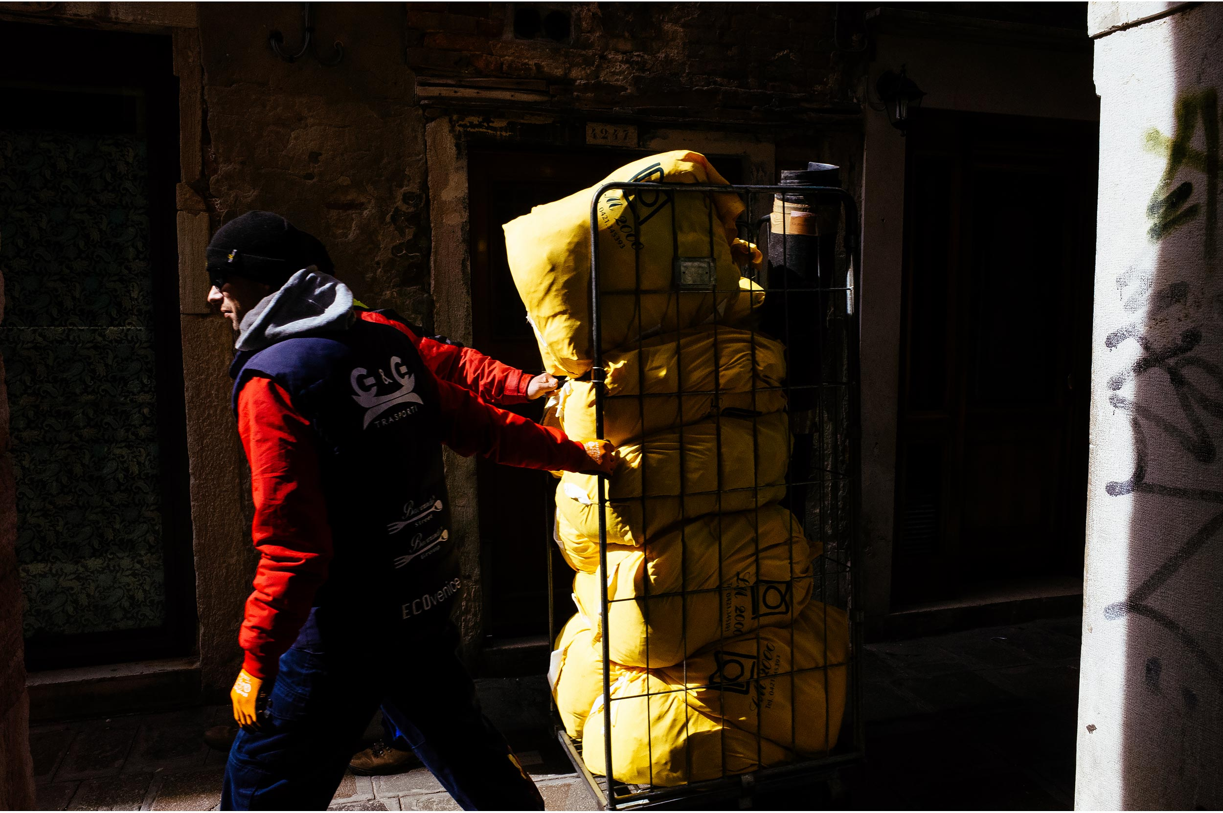 Venice, Italy, 2016. Two workers carrying some stuff look like one having three arms.