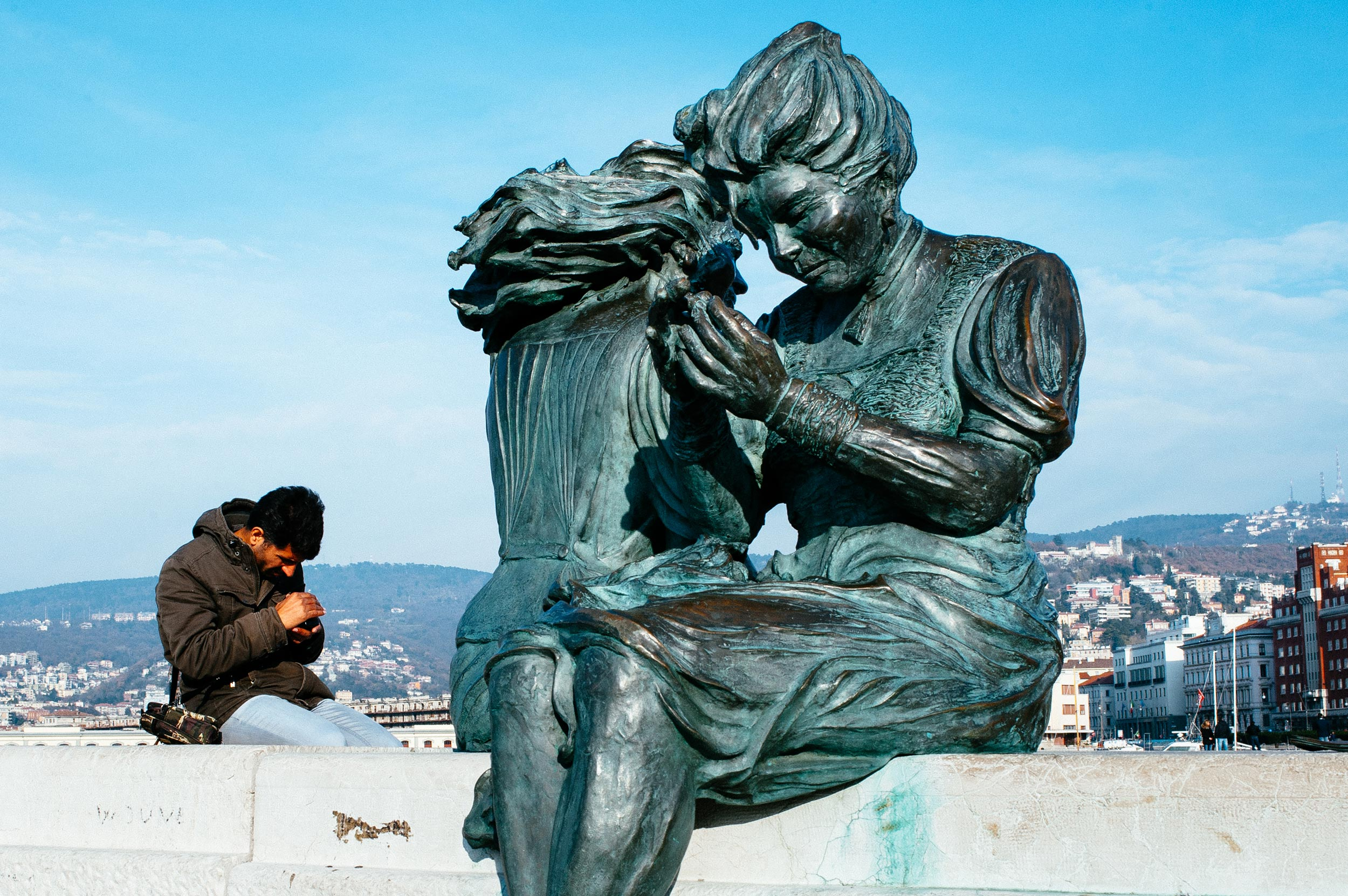 Trieste, Italy, 2015. A man looking at his smartphone has the same pose as a bronze statue near him.
