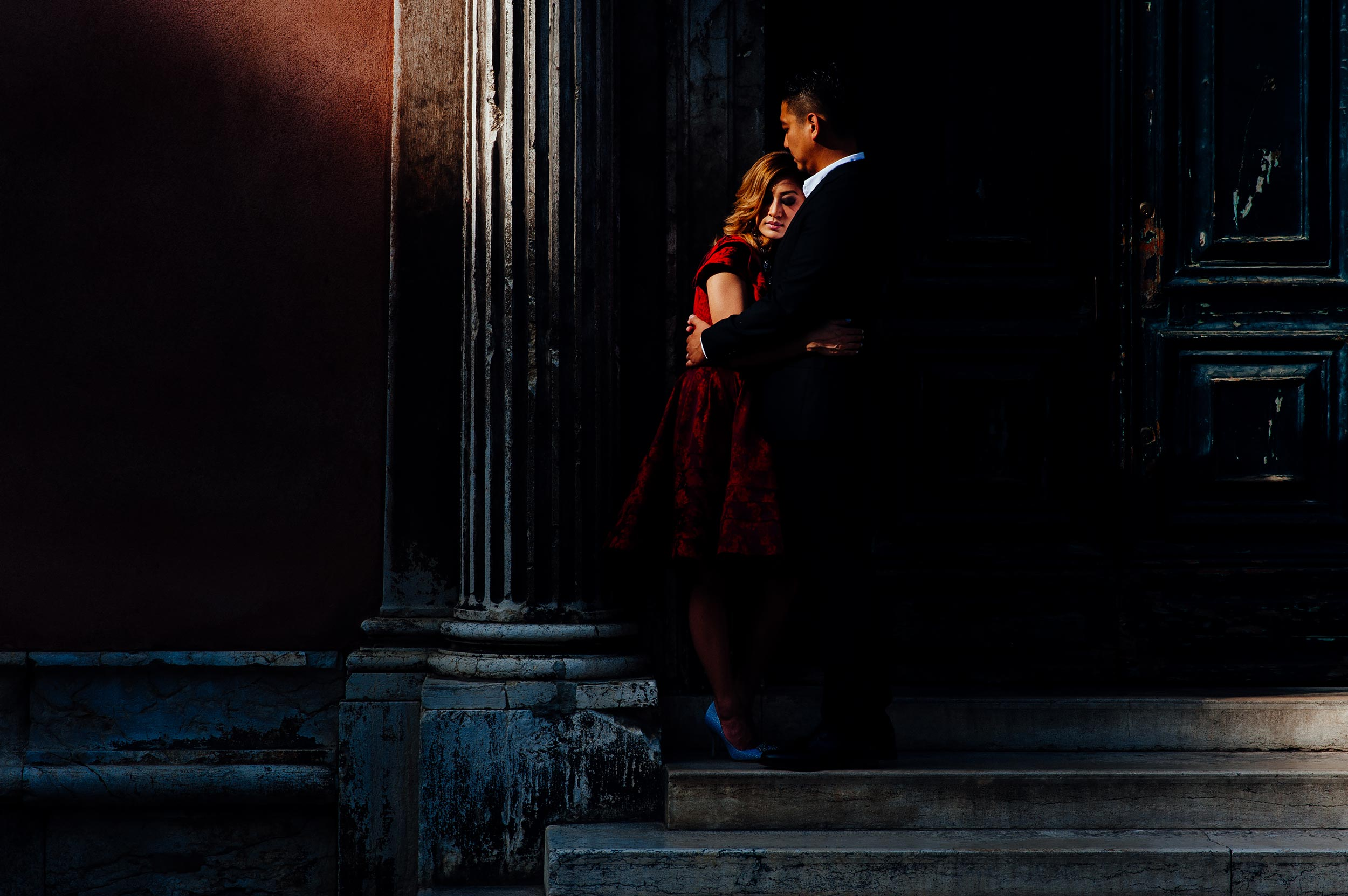engagement-photographer-venice-couple-hugs-in-a-ray-of-light-red-dress.jpg