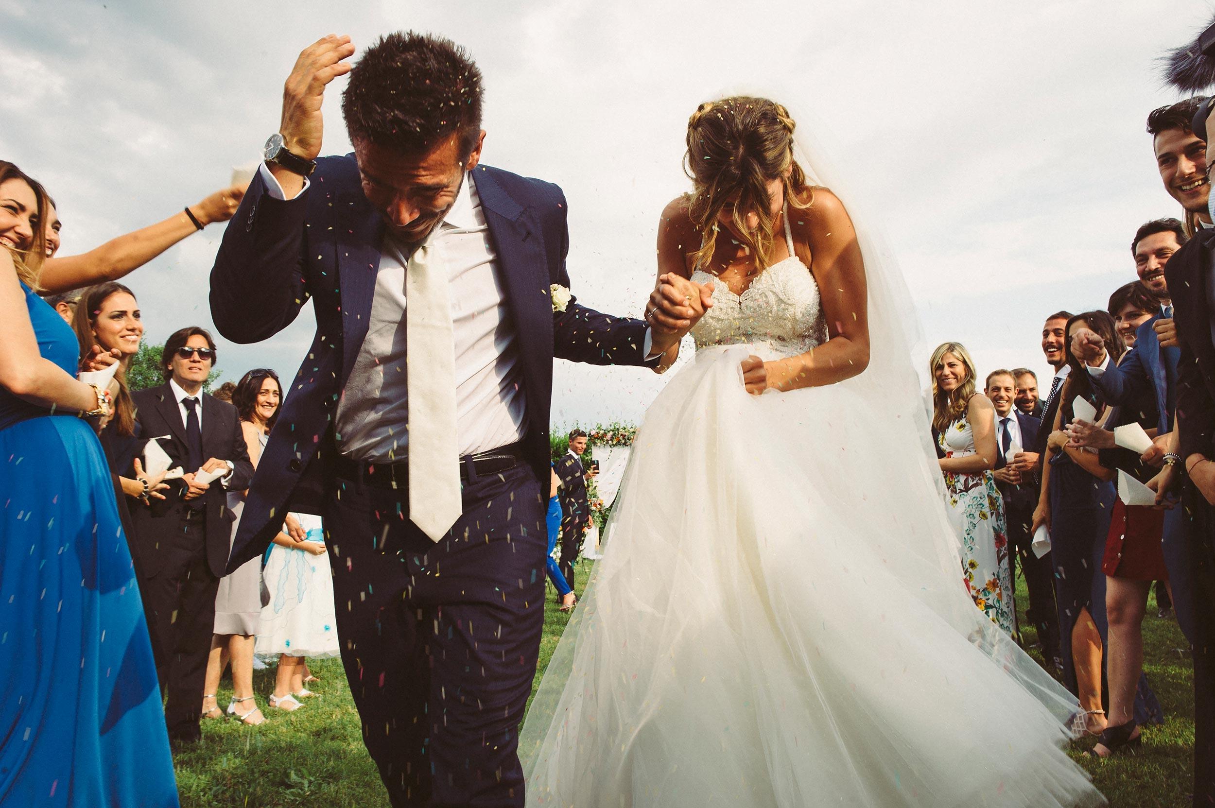 wedding-ceremony-garden-italy-bride-and-groom-running-confetti-rice-documentary-wedding-photography-by-Alessandro-Avenali.jpg