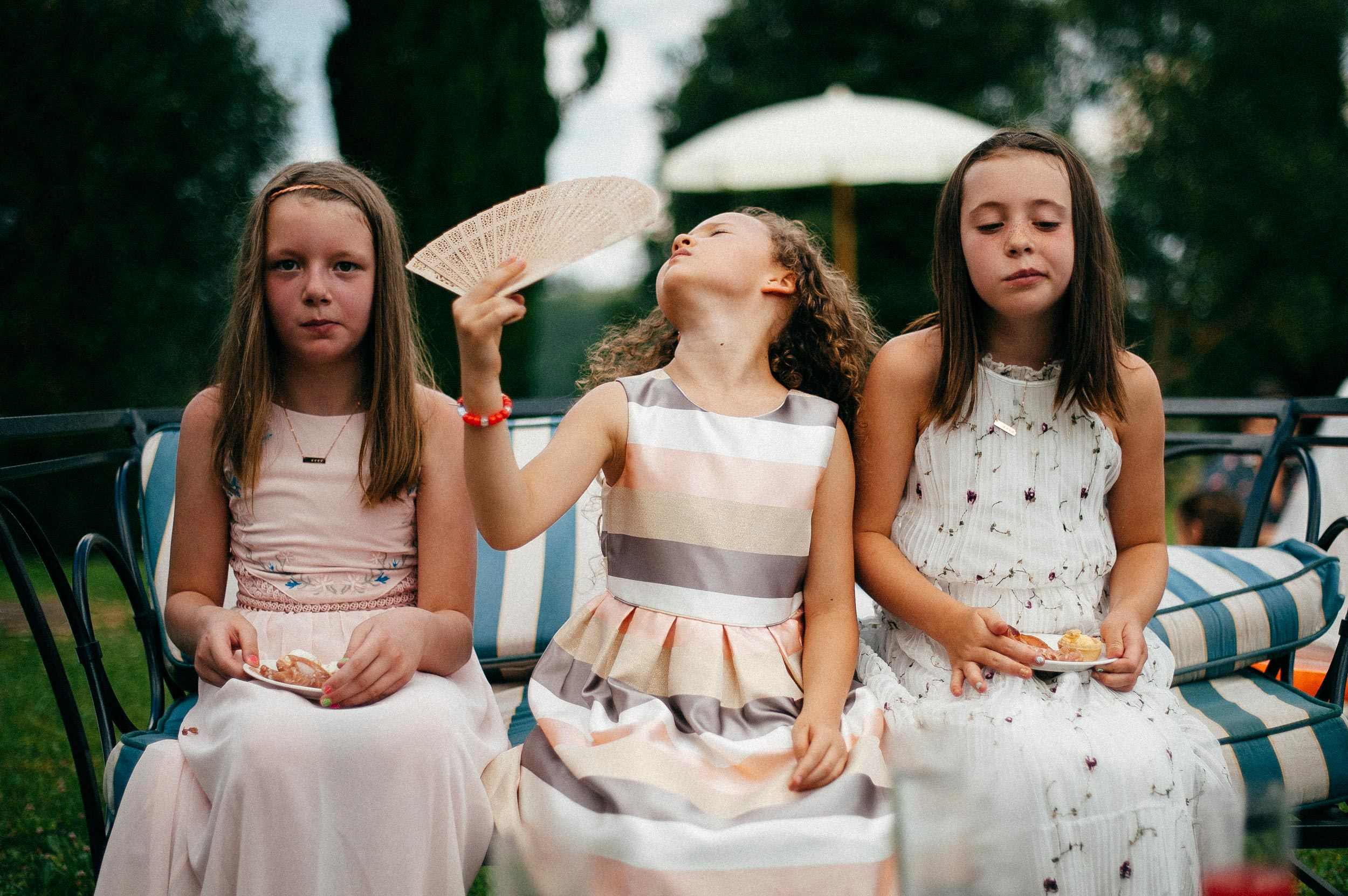girls-at-the-reception-using-fan-hot-weather-documentary-wedding-photography-in-tuscany-by-Alessandro-Avenali.jpg