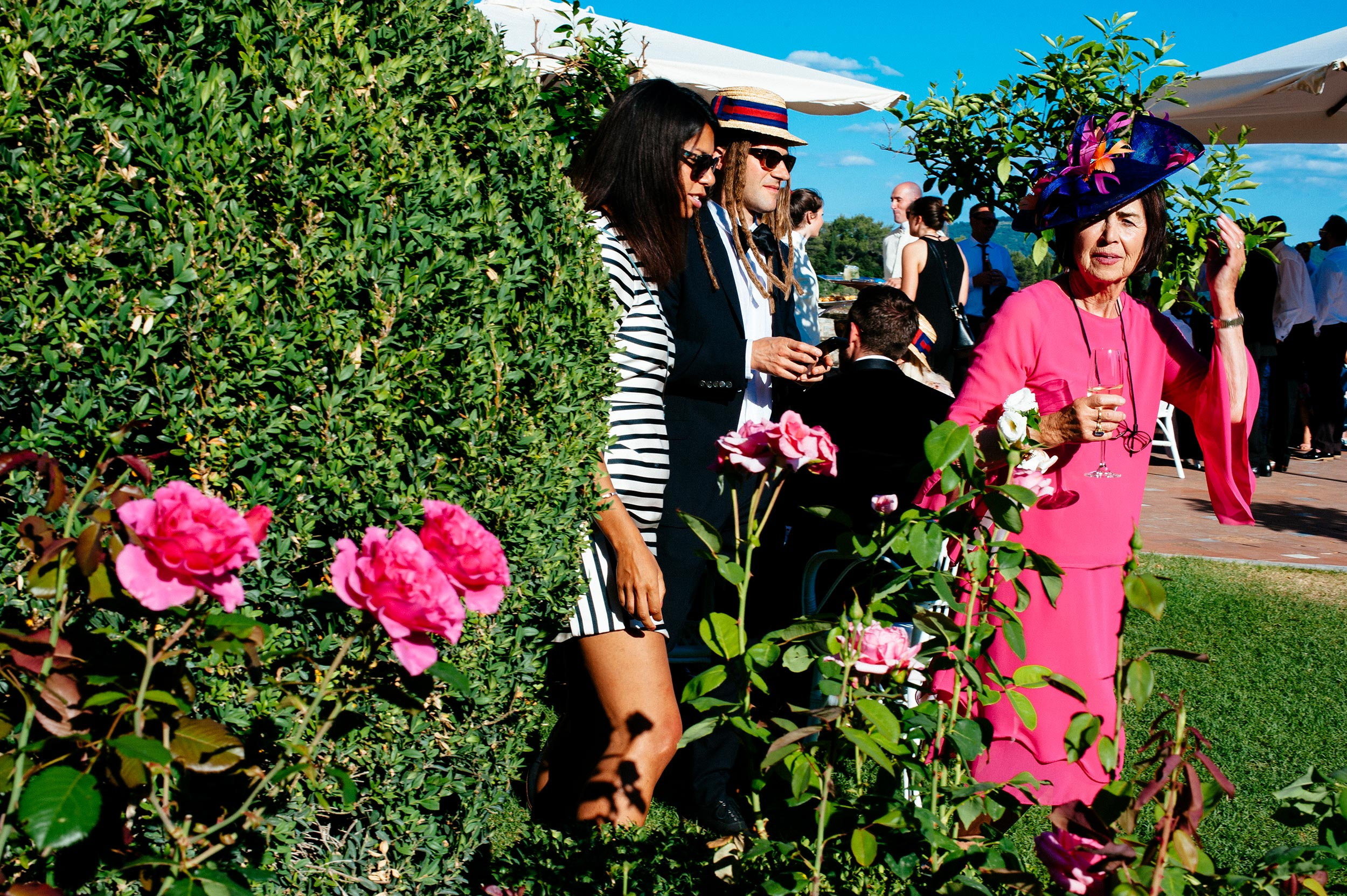 lady-dressed-in-magenta-next-to-magenta-roses-at-reception-documentary-street-wedding-photography-by-Alessandro-Avenali.jpg