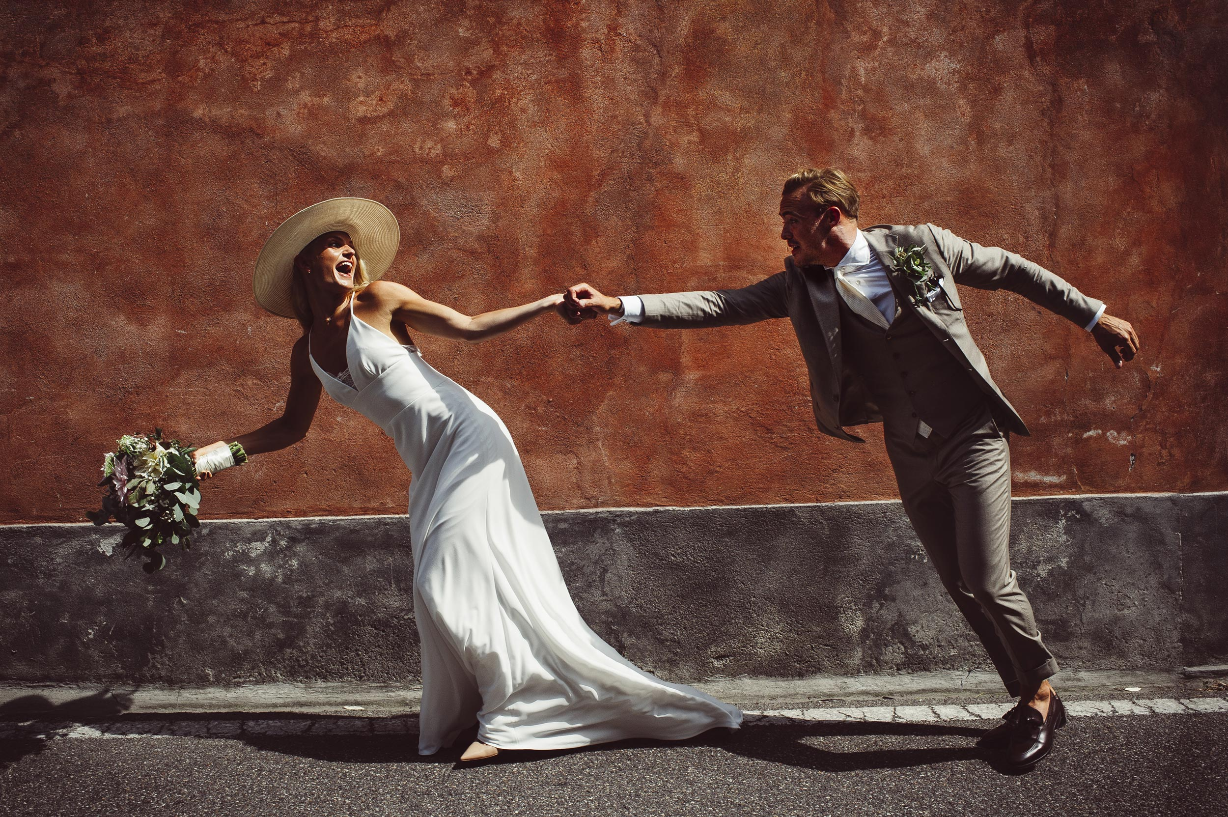 lake-como-wedding-photographer-Alessandro-Avenali-bride-with-hat-grabs-the-groom-running-against-a-red-wall.jpg