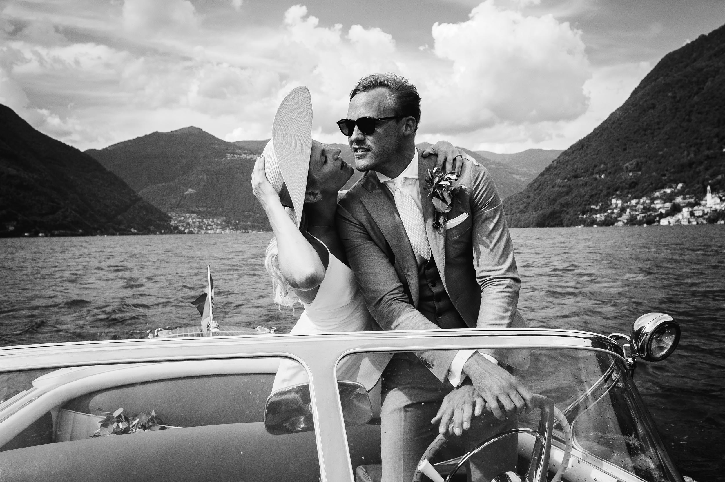 lake-como-wedding-photographer-Alessandro-Avenali-bride-and-groom-driving-riva-yacht-motorboat-black-and-white.jpg