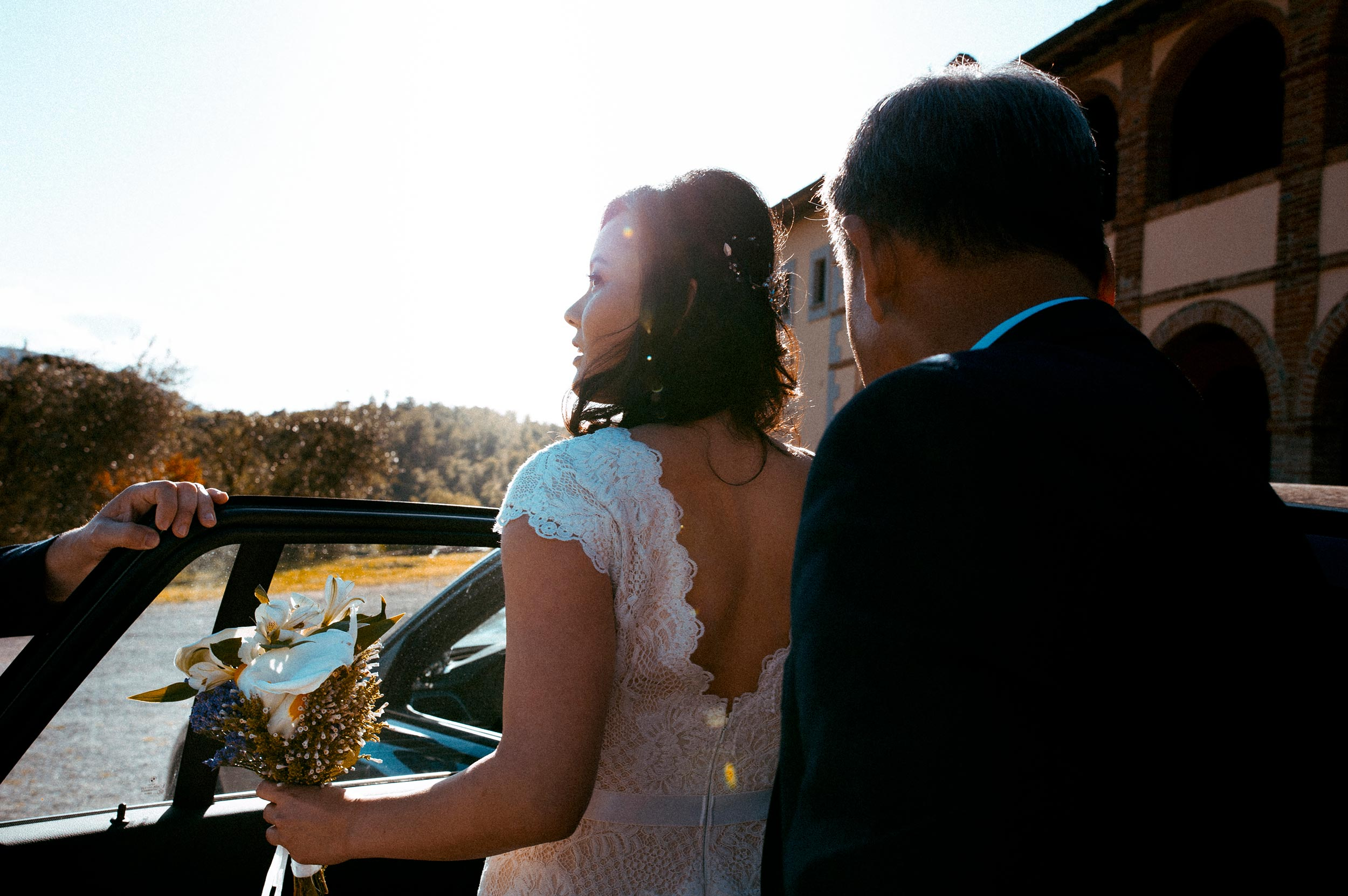 American Korean bride enters the car while looking at the Ceremony place Tuscany Wedding in Siena by Alessandro Avenali