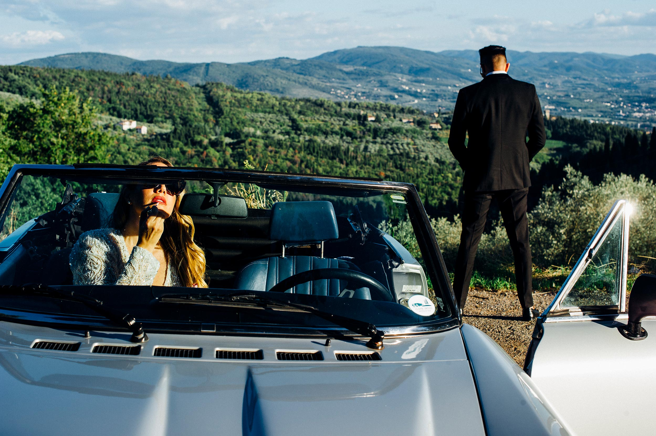 bride putting lipstick on while the groom is pissing on the side of the road vintage convertible in tuscany