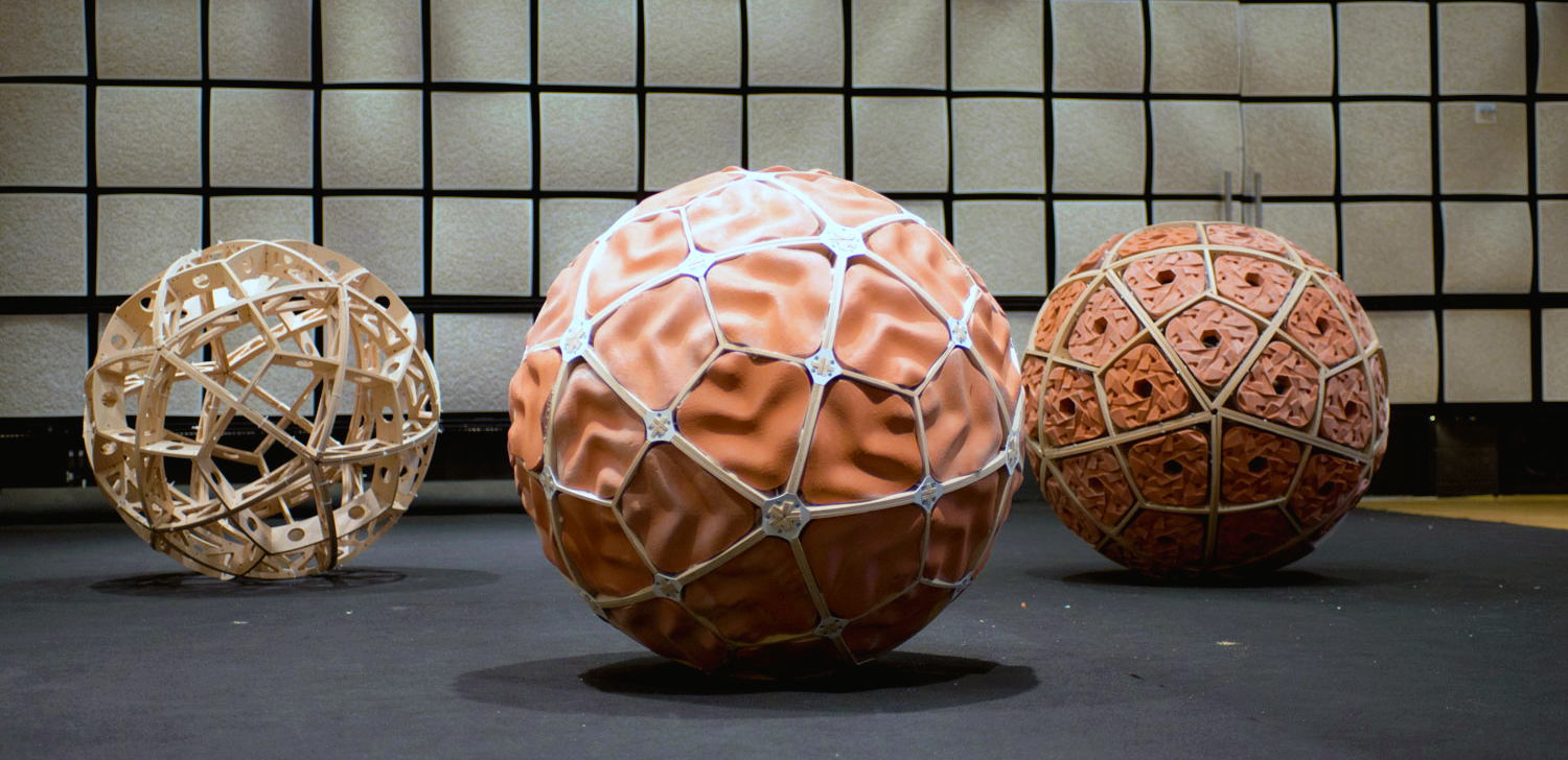 TZ'IJK.2.  Two finished robots with different tile design and one wooden spherical structure.